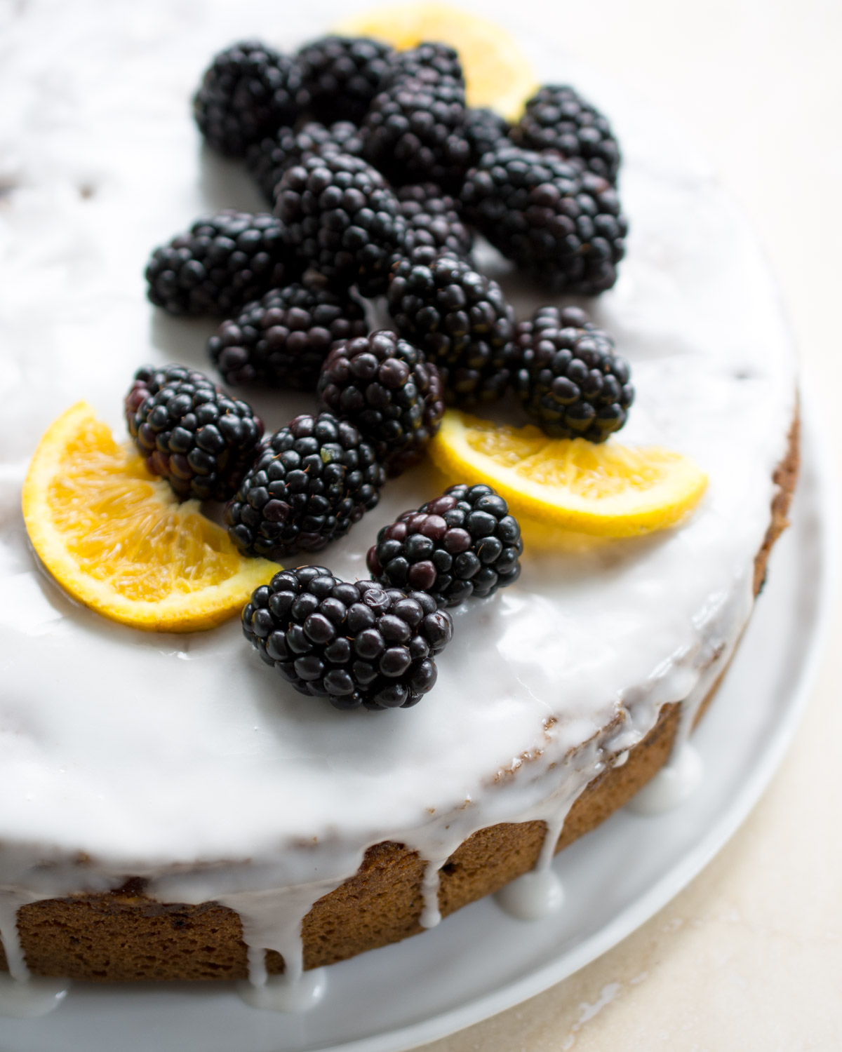 Just glazed orange blackberry cake. Garnished with fresh blackberries and orange slices.