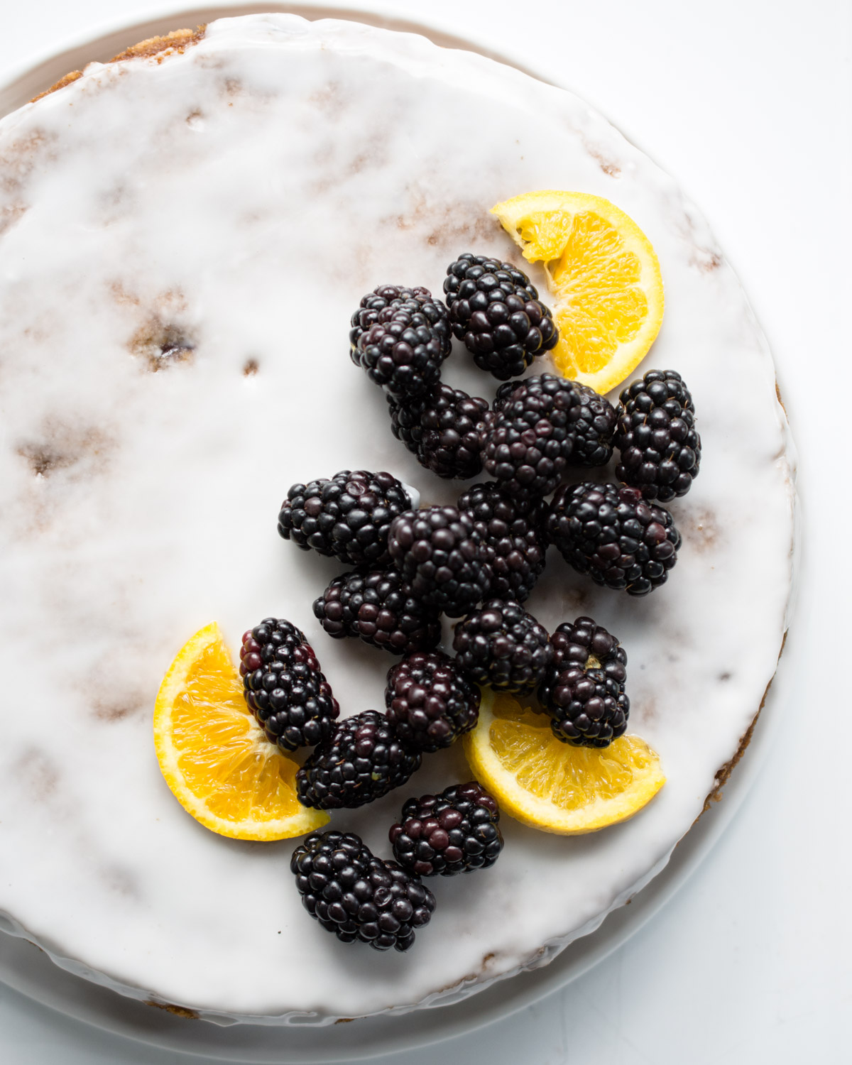 Orange Blackberry Olive oil Cake garnished with fresh blackberries and orange slices.