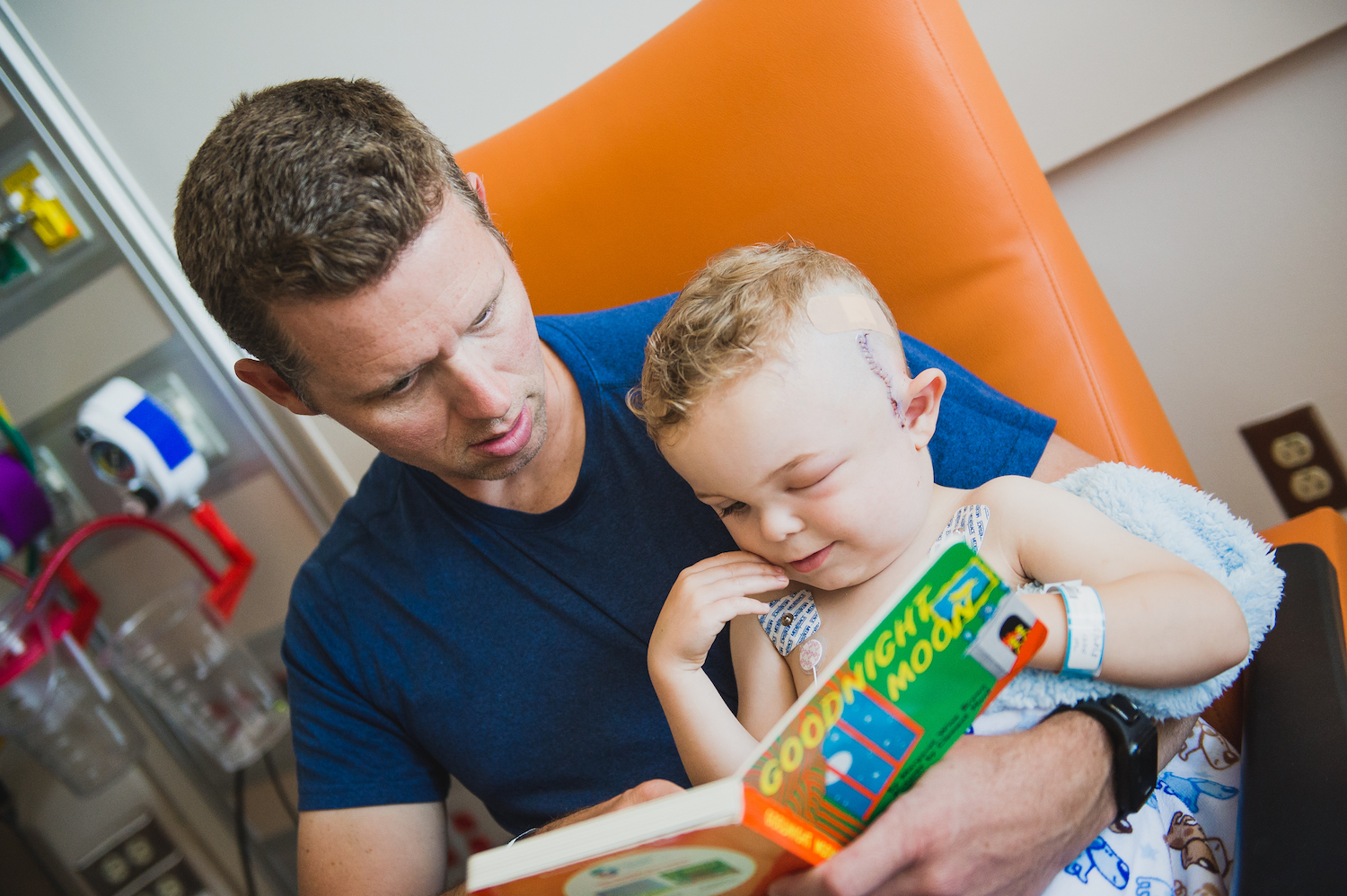 Injured Boy and his Father Read a Book Together.jpg