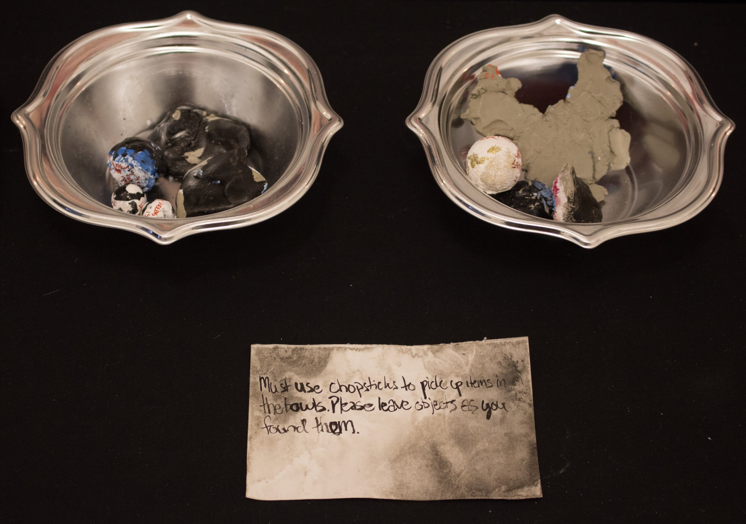 - In this installation, I included a participatory component, which take the form of the two bowls of small objects. To view the objects, one is only permitted to do so if one is capable of picking them up with chopsticks. On the other side of the objects, there may be some imagery or text describing my own experience with holding these identities.