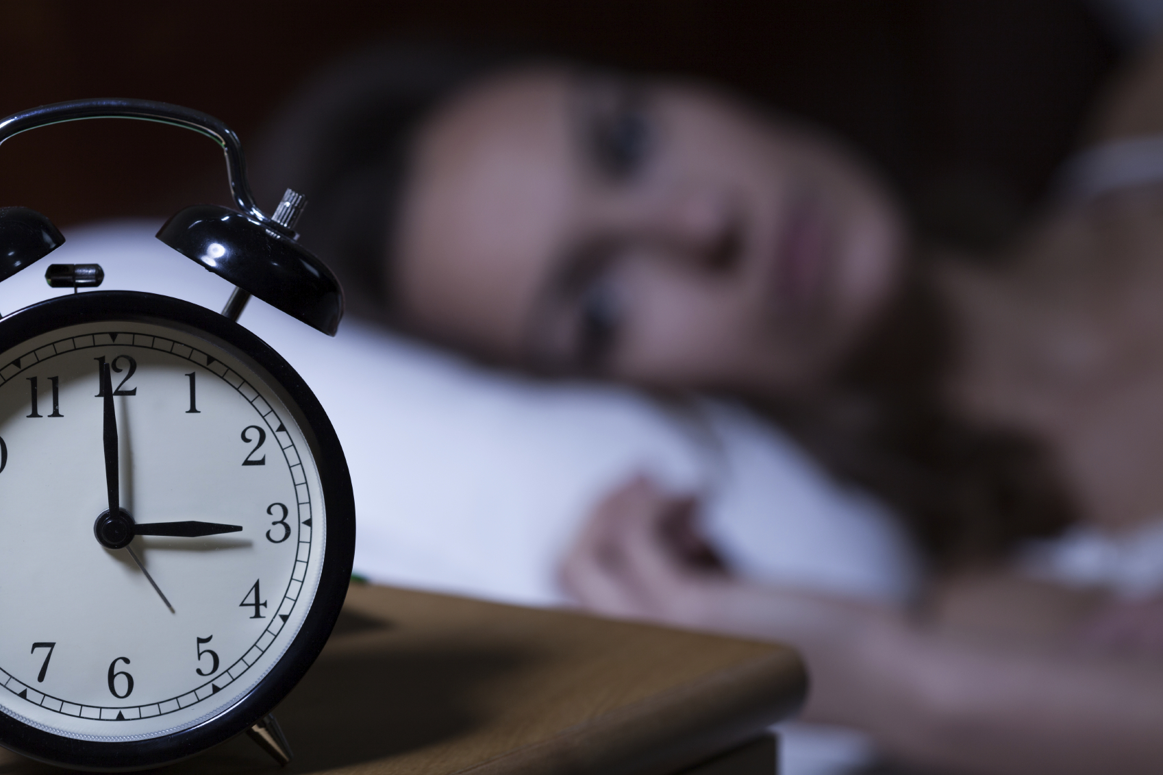 woman with insomnia staring at clock