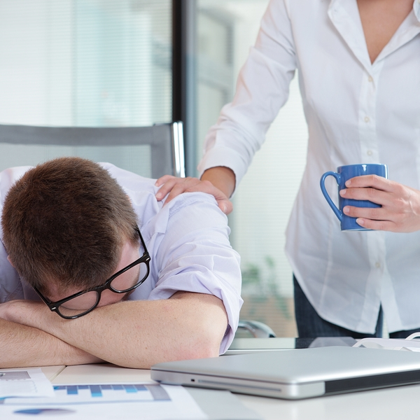 woman waking up man with daytime sleepiness at his desk