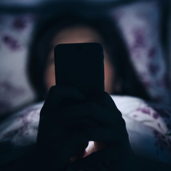 woman in bed with mobile device unable to sleep