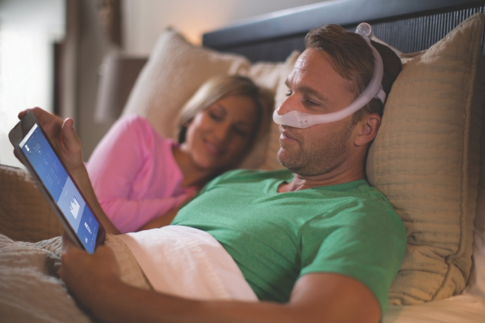 man laying in bed with cpap mask