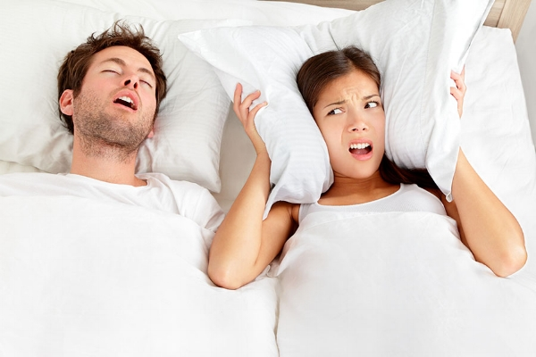 Man snoring, man with sleep apnea, wife annoyed by snoring