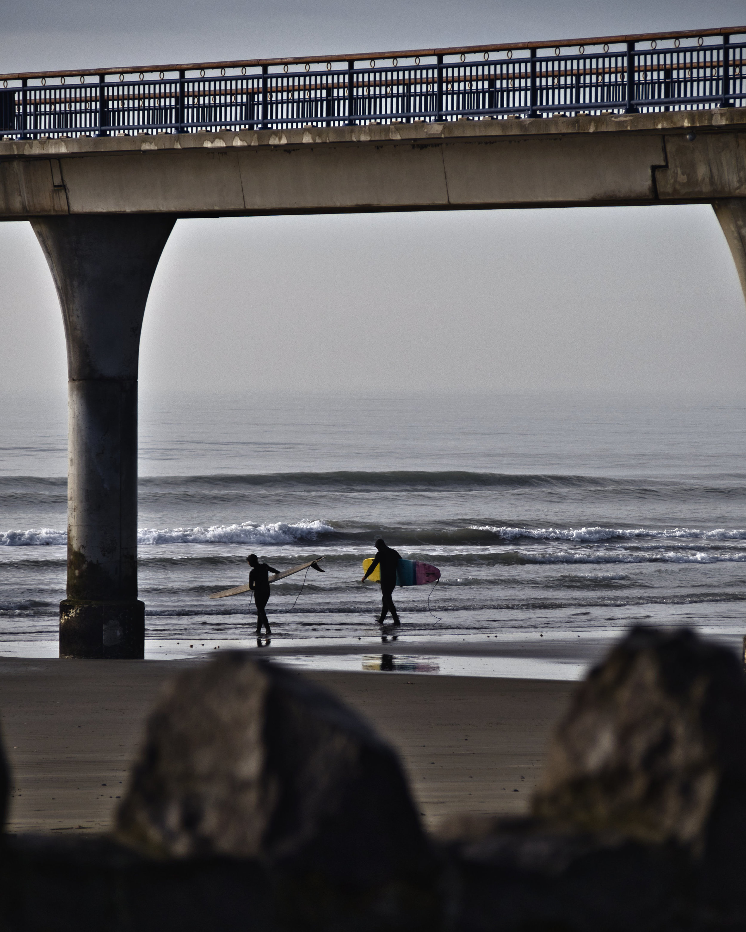 Two dedicated surfers make their way out to the beach break beneath New Brighton Pier on this Christchurch beach on a chilly July morning.