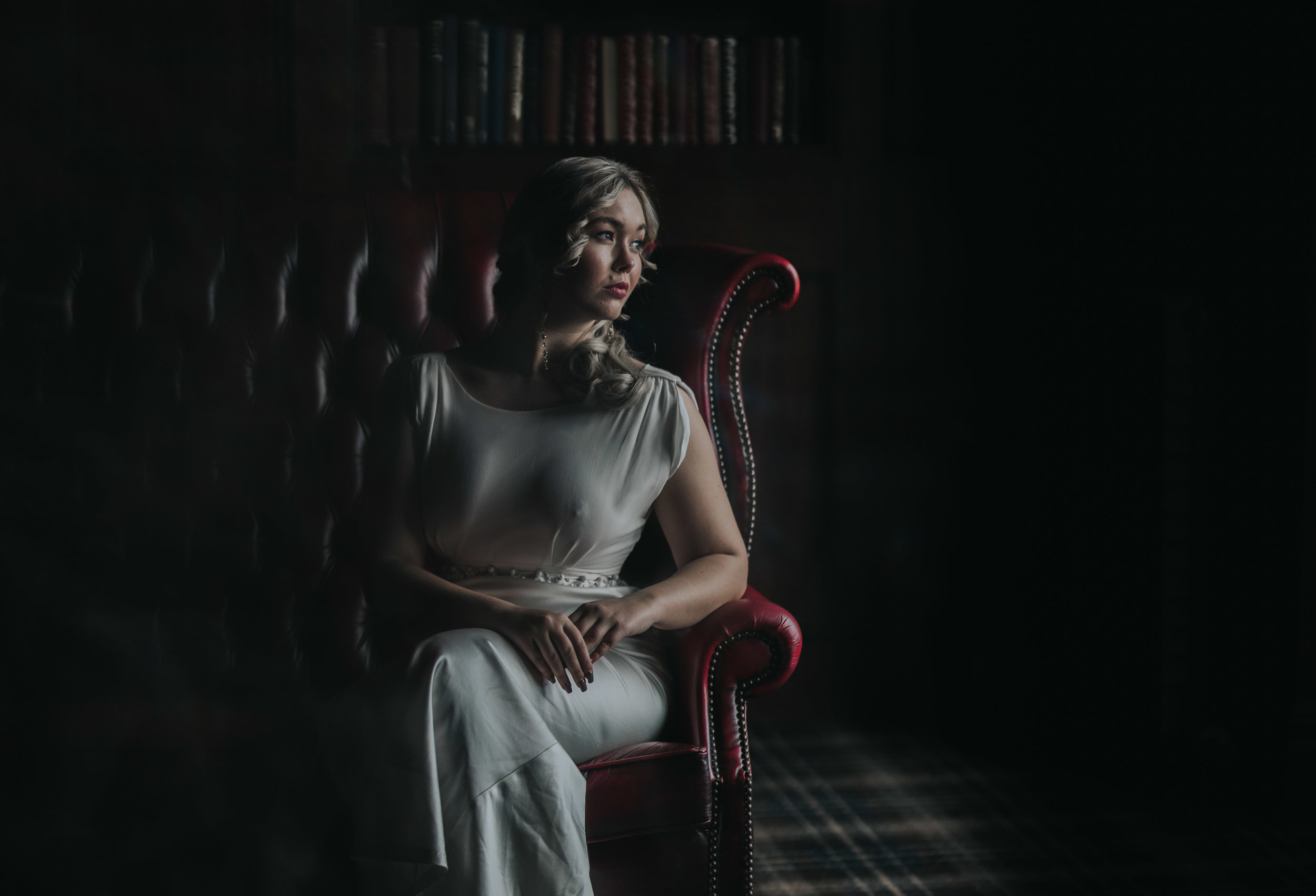 Bride sits on a dark red leather chair looking out of the window with the light flooding her face. The rest of the room is dark.