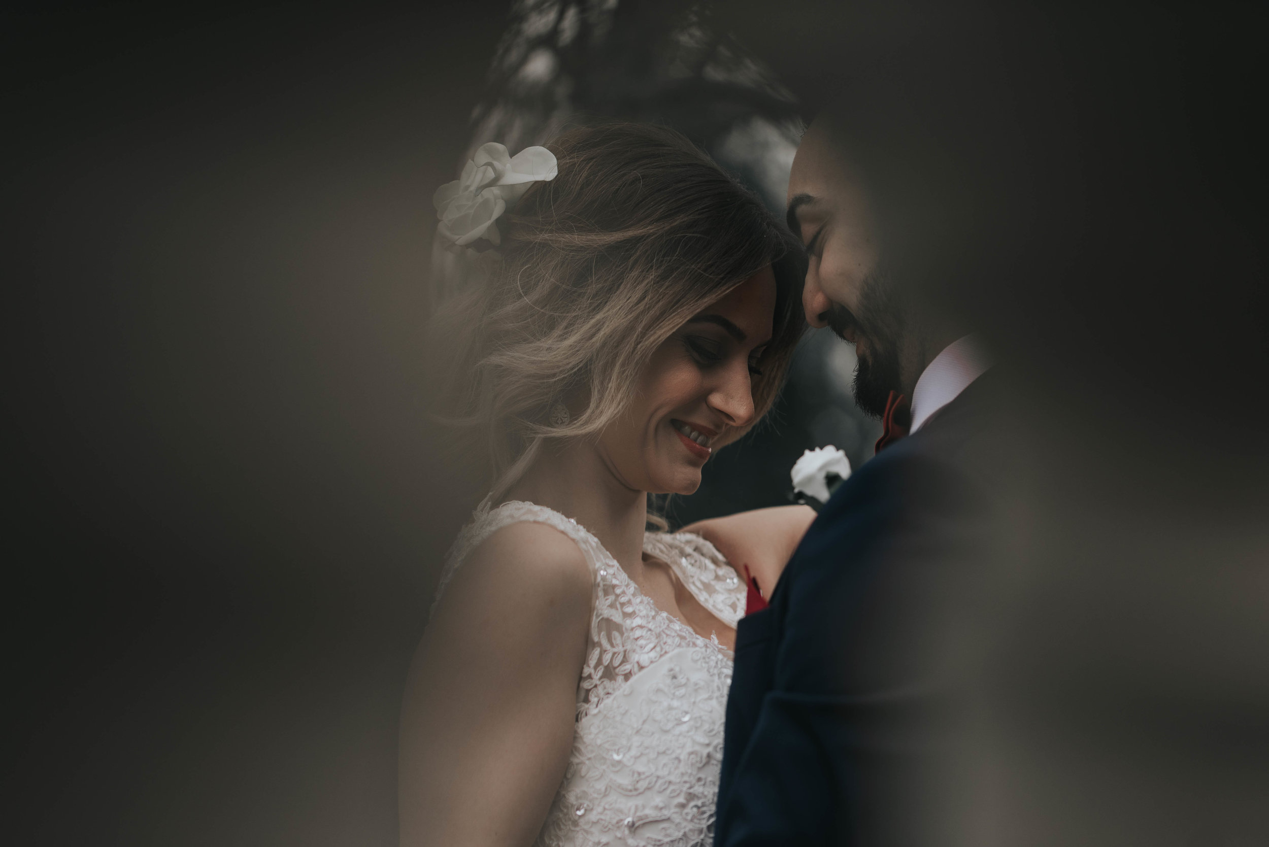 bride and groom have a cheeky giggle together, outside with the soft sunlight lighting their faces