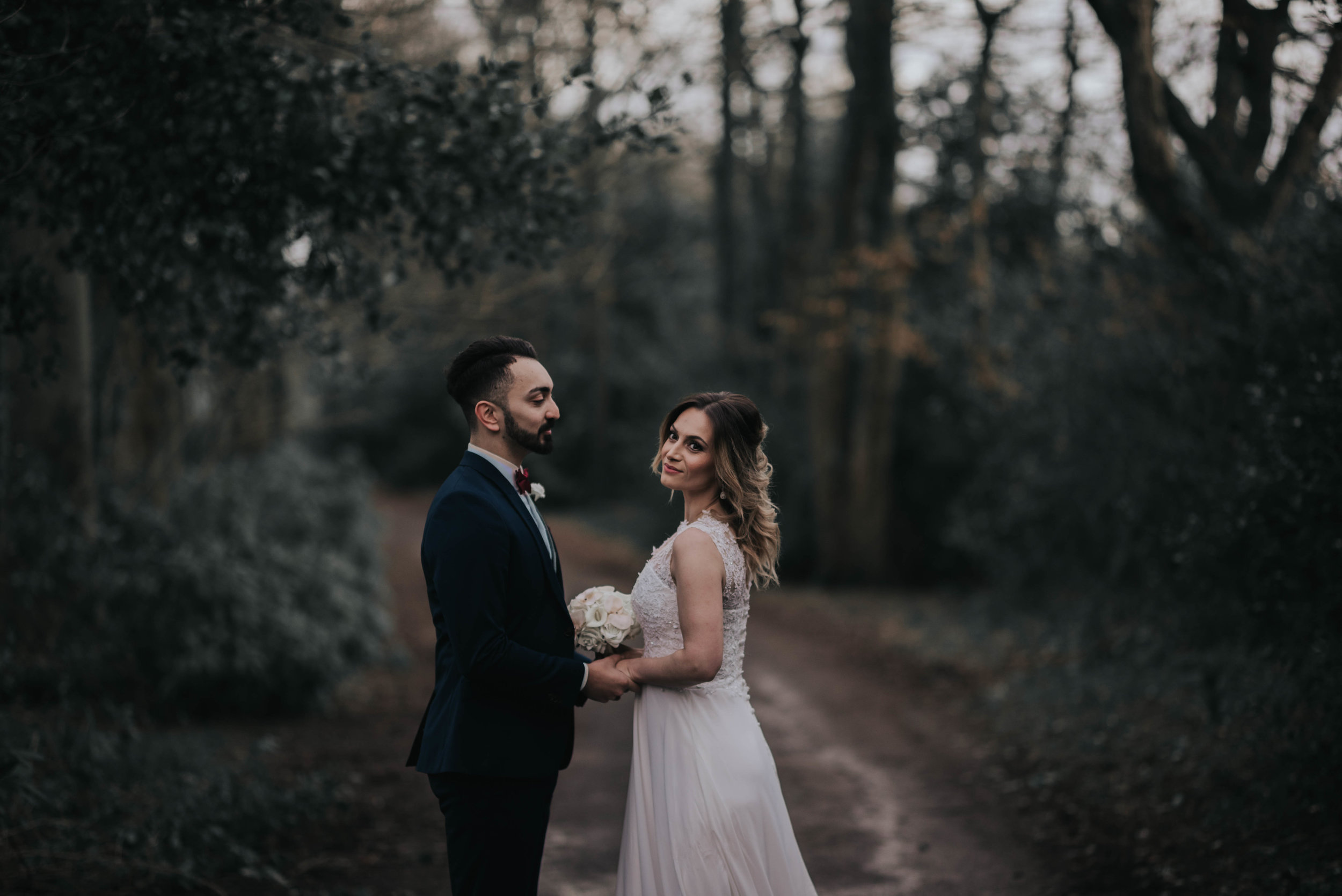 the bride and groom stand facing each other in woodland at Ashfield house