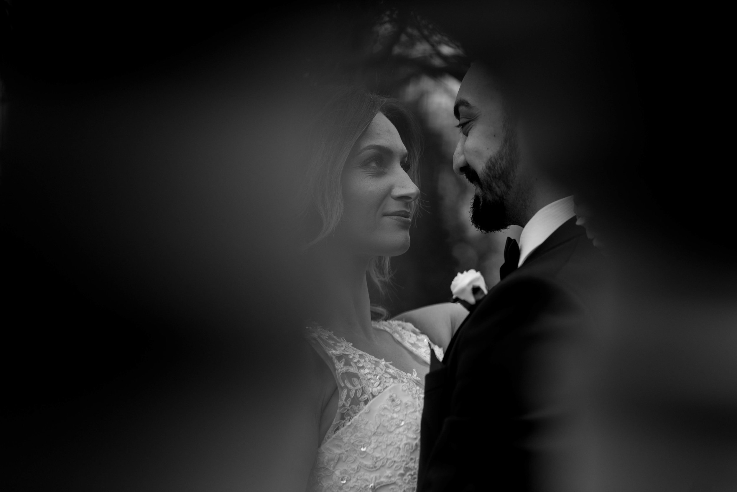 the bride and groom have an intimate moment  - photo shot between a couple of pillars at Ashfield House