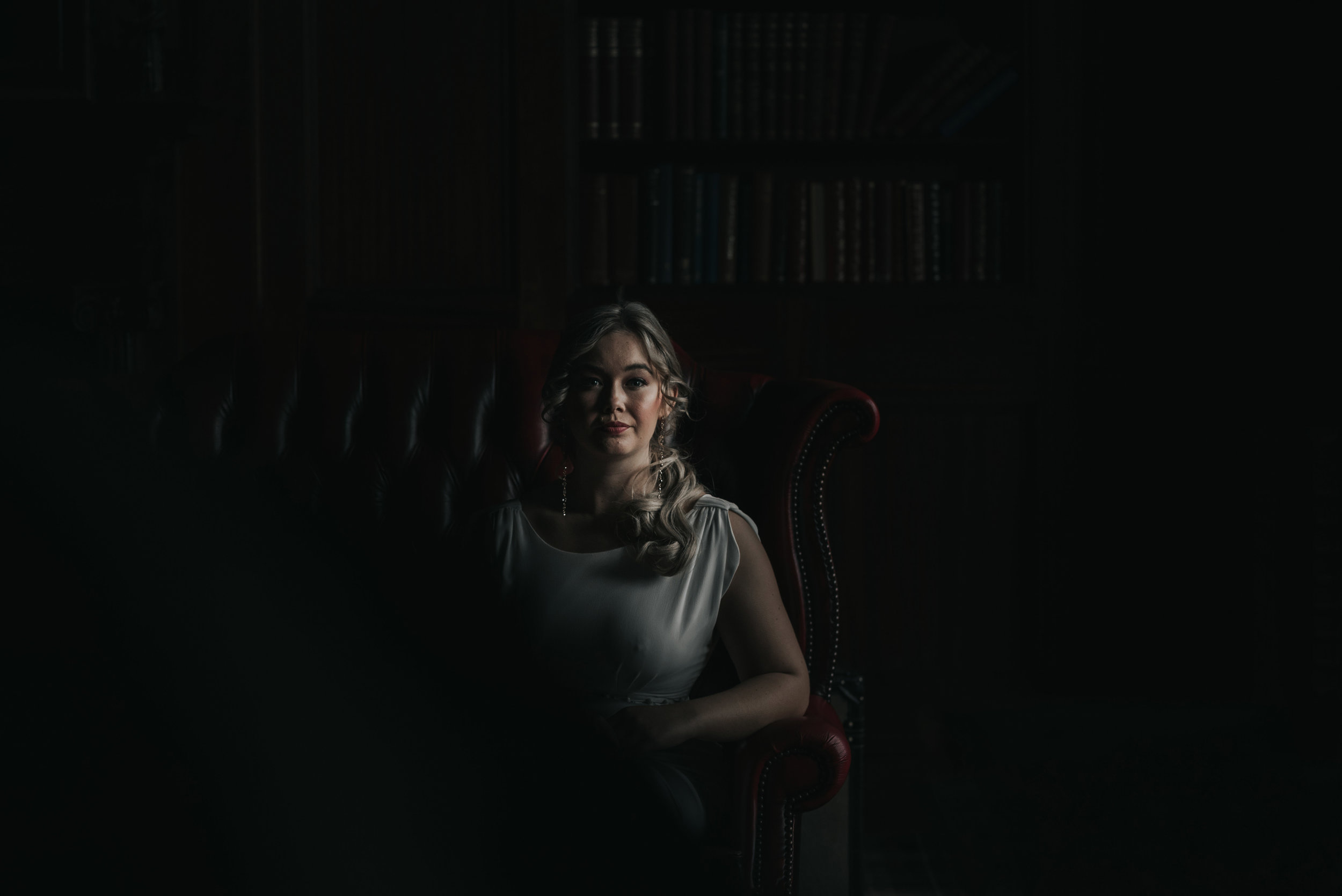the bride looks directly at the camera for a shot in semi-darkness on a red leather sofa in ashfield House