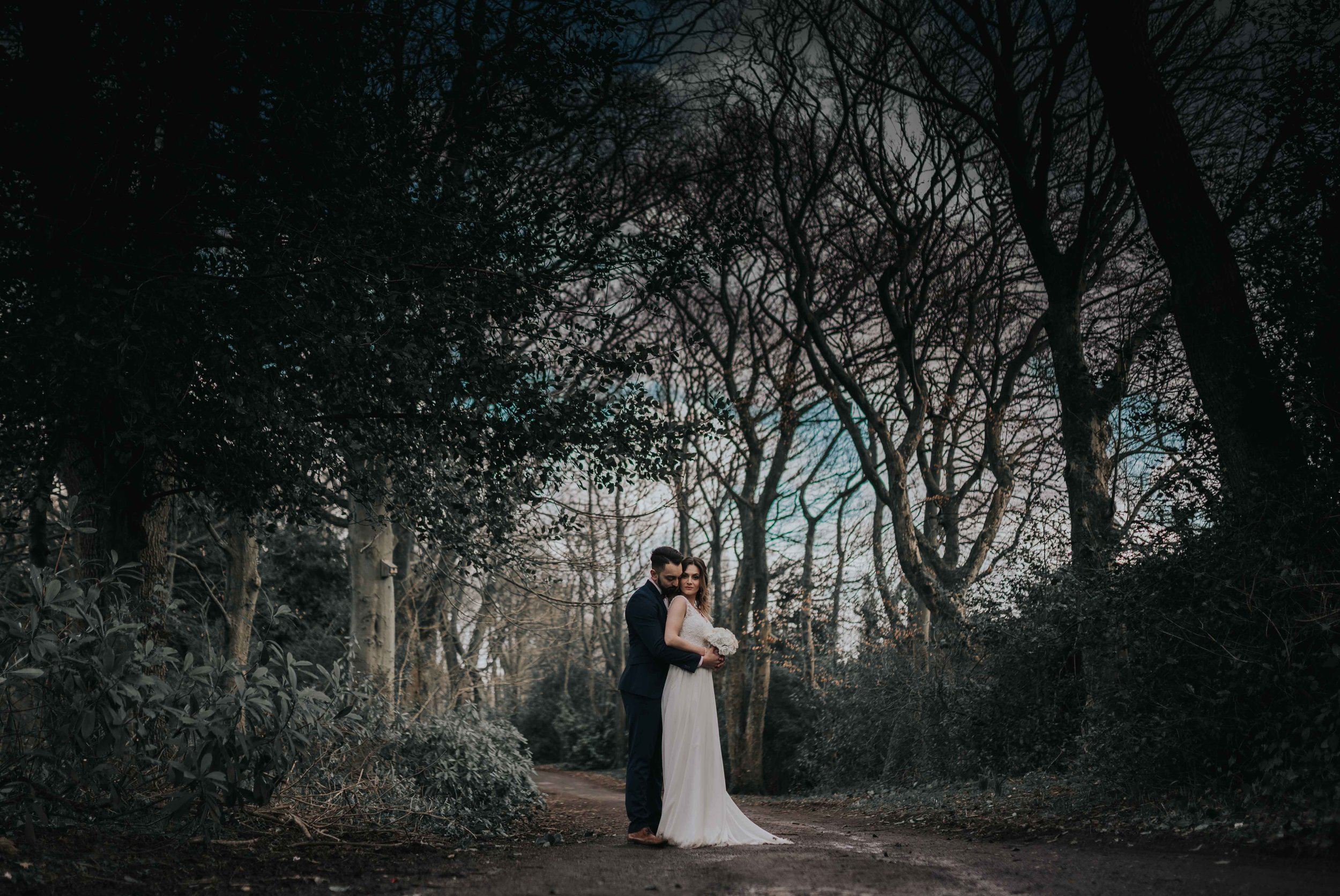 the bride and groom stand central in the image, in the woods surrounding ashfield house