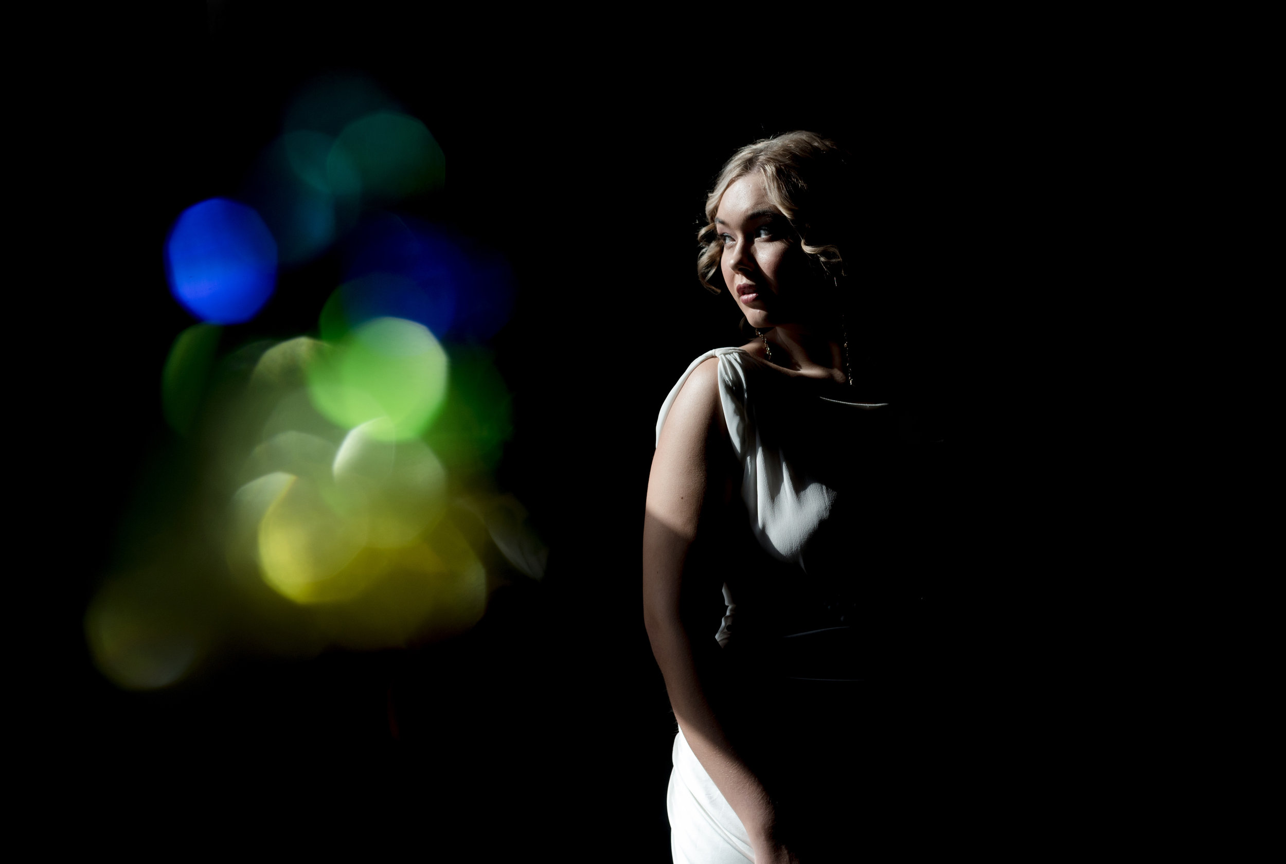 the bride stands in the window while light from the sun reflects through a prism, casting colour in the image