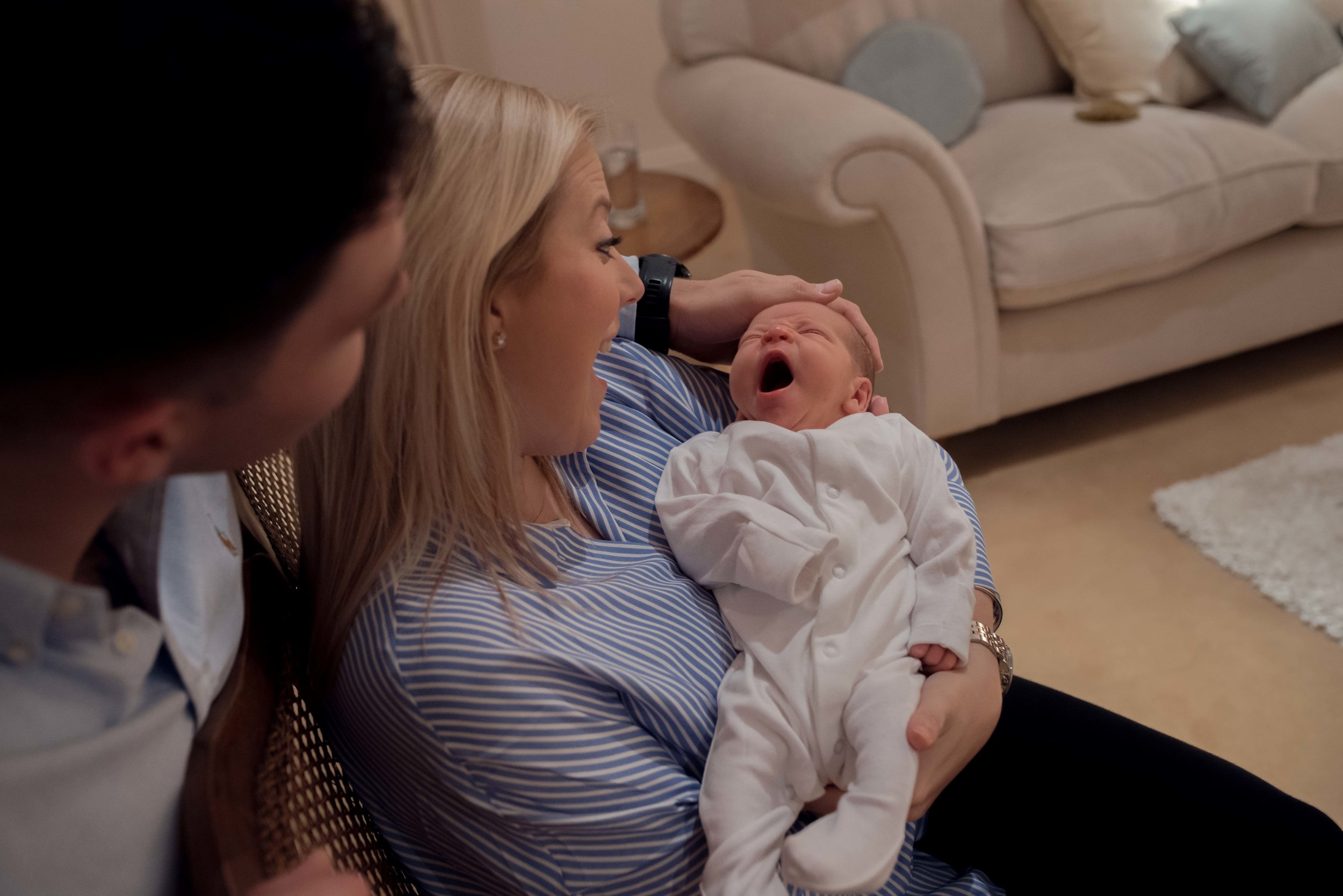 Newborn baby Harry yawn as his mum and dad look lovingly at him.