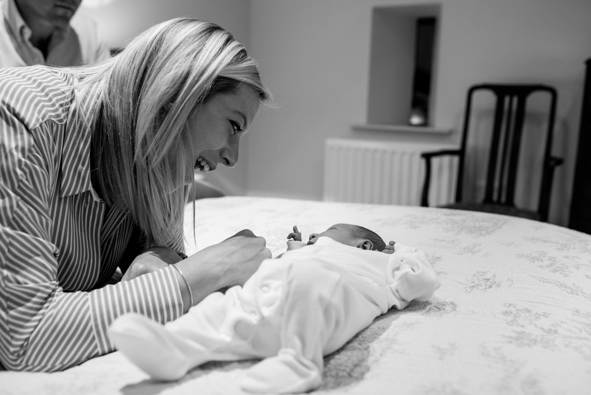 New mum Chloe plays with her newborn son as he lies on the bed.