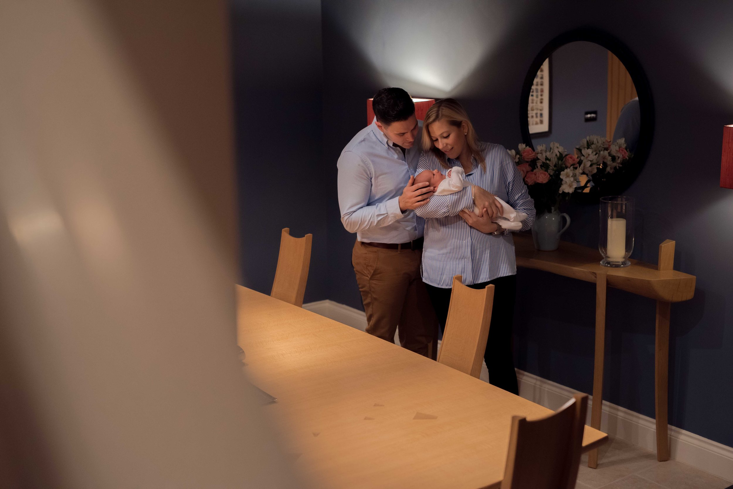 Newborn baby Harry is cuddled by his mum and dad as they stand and have a quiet moment in their dining room.