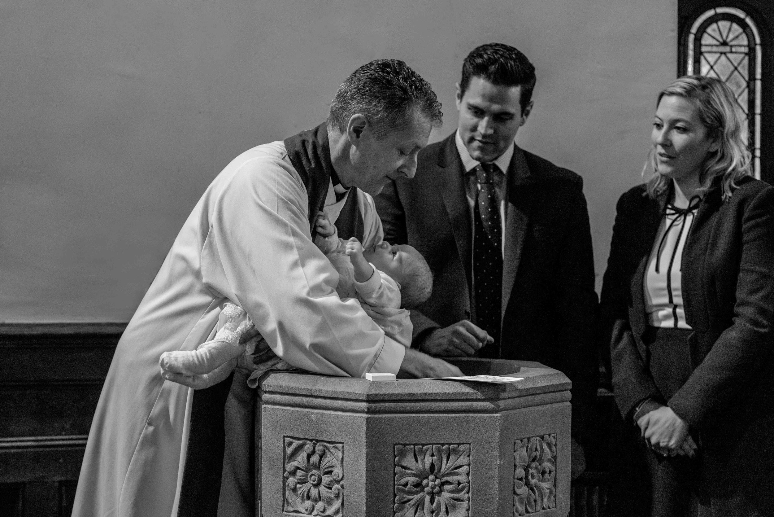 The vicar Christens baby Harry in the front at the rear of the church.