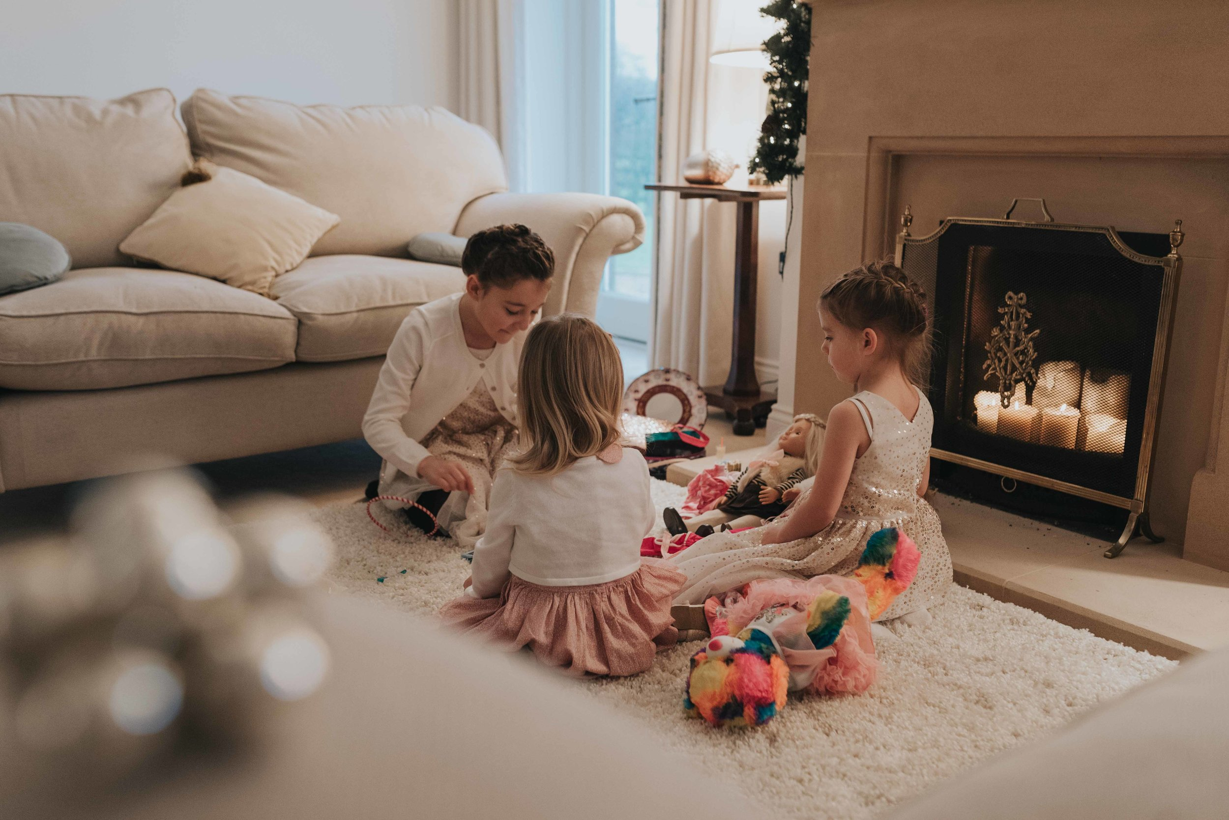 Three children sit together on a rug in front of the fireplace during Christening celebrations.