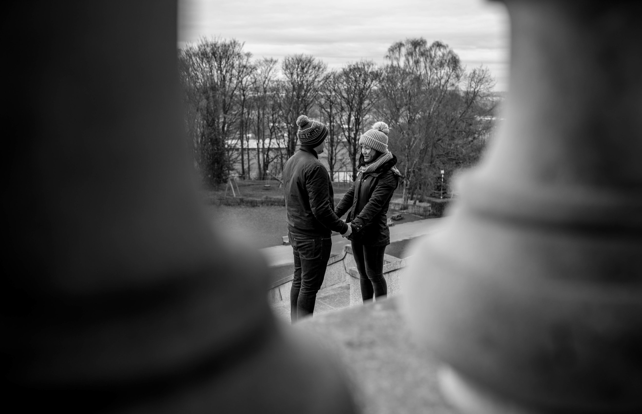 The bride and groom stand on the steps of the Ashton Memorial in Lancaster, looking at each other through stone pillars.