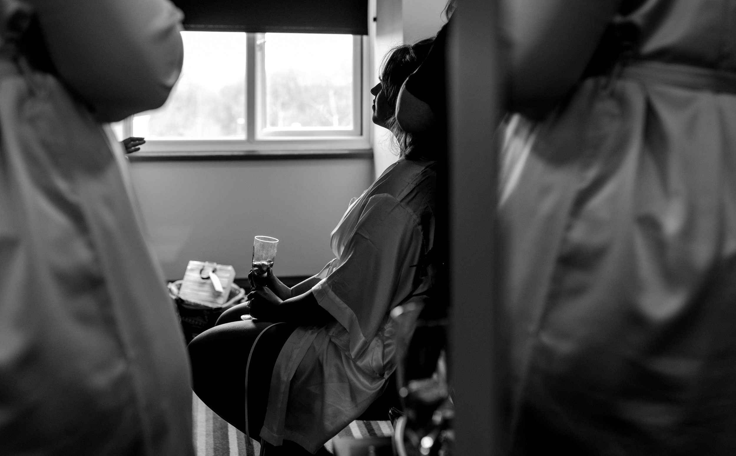 The bride sits lit up with light from the window while she has her makeup done