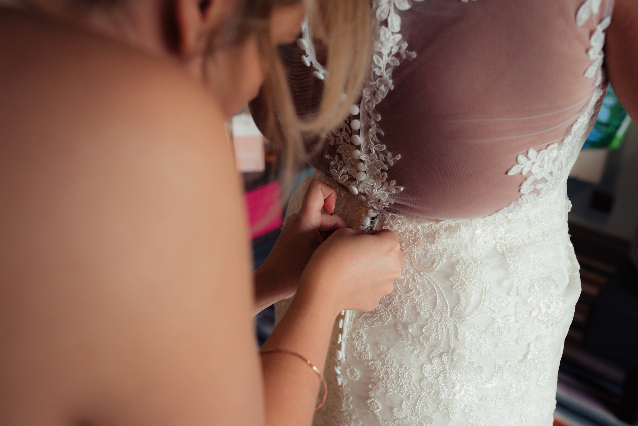 a bridesmaid buttons up the brides stunning lace dress