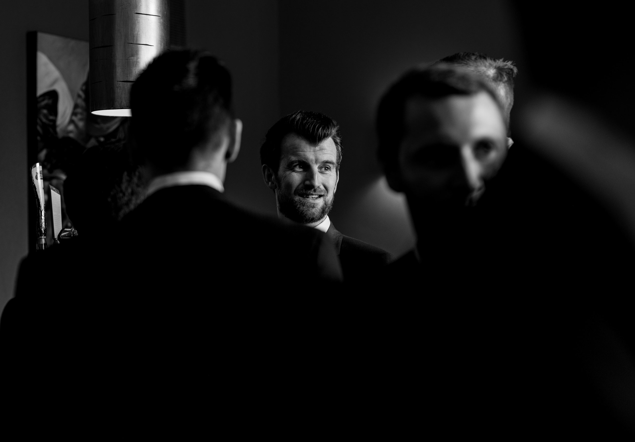 a male wedding guest lit up with the sunlight coming through the window