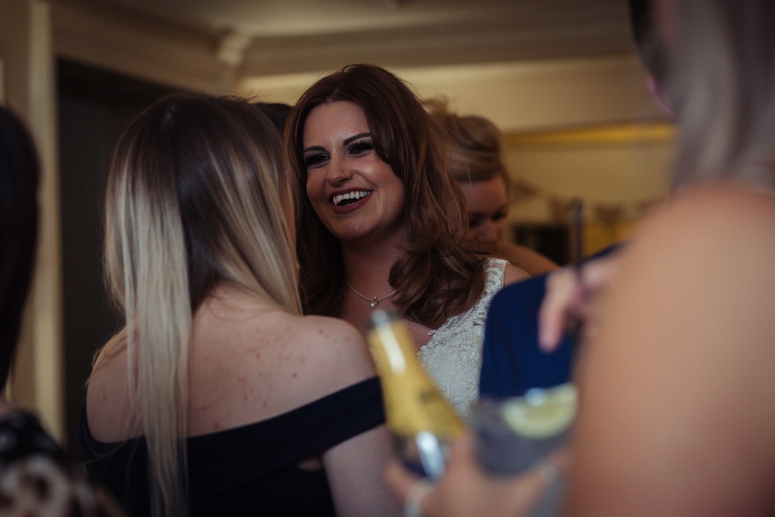 the bride stands chatting to her female friends in the bar