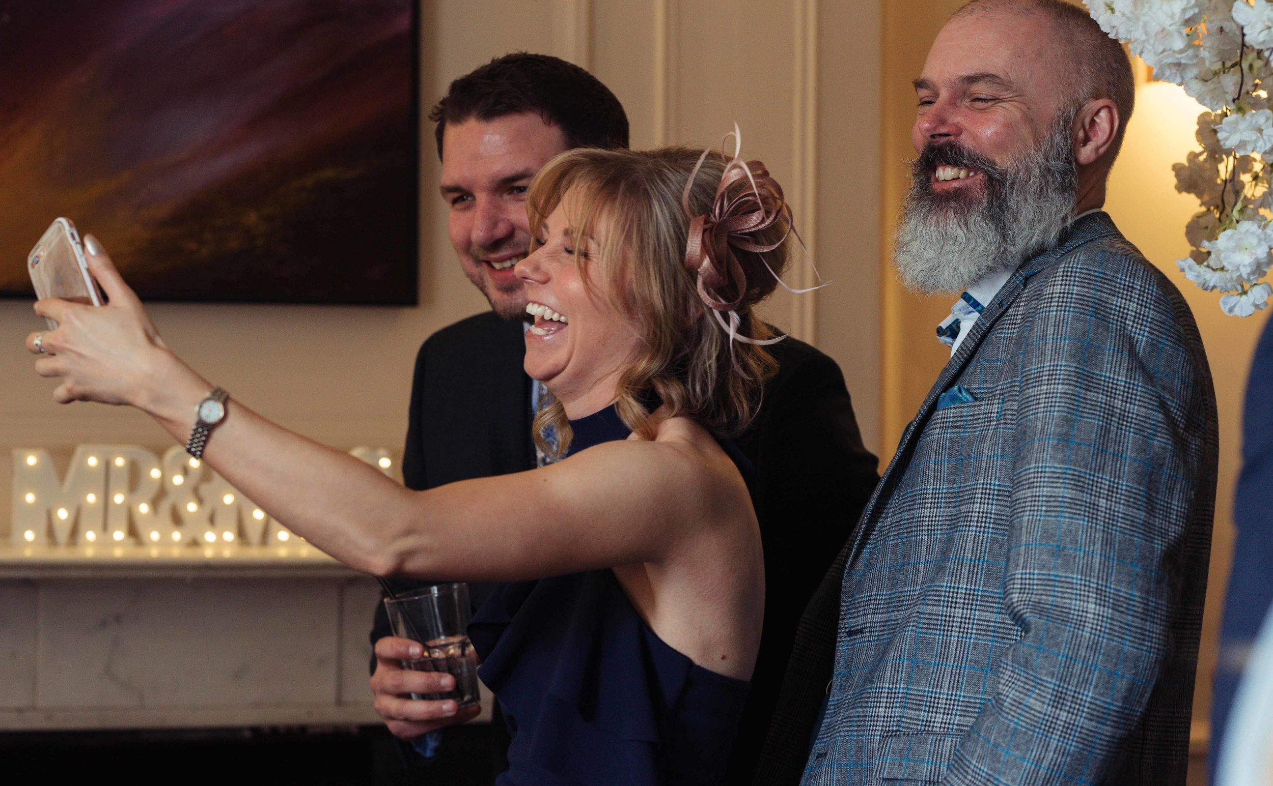 three guests take a selfie during the drinks reception