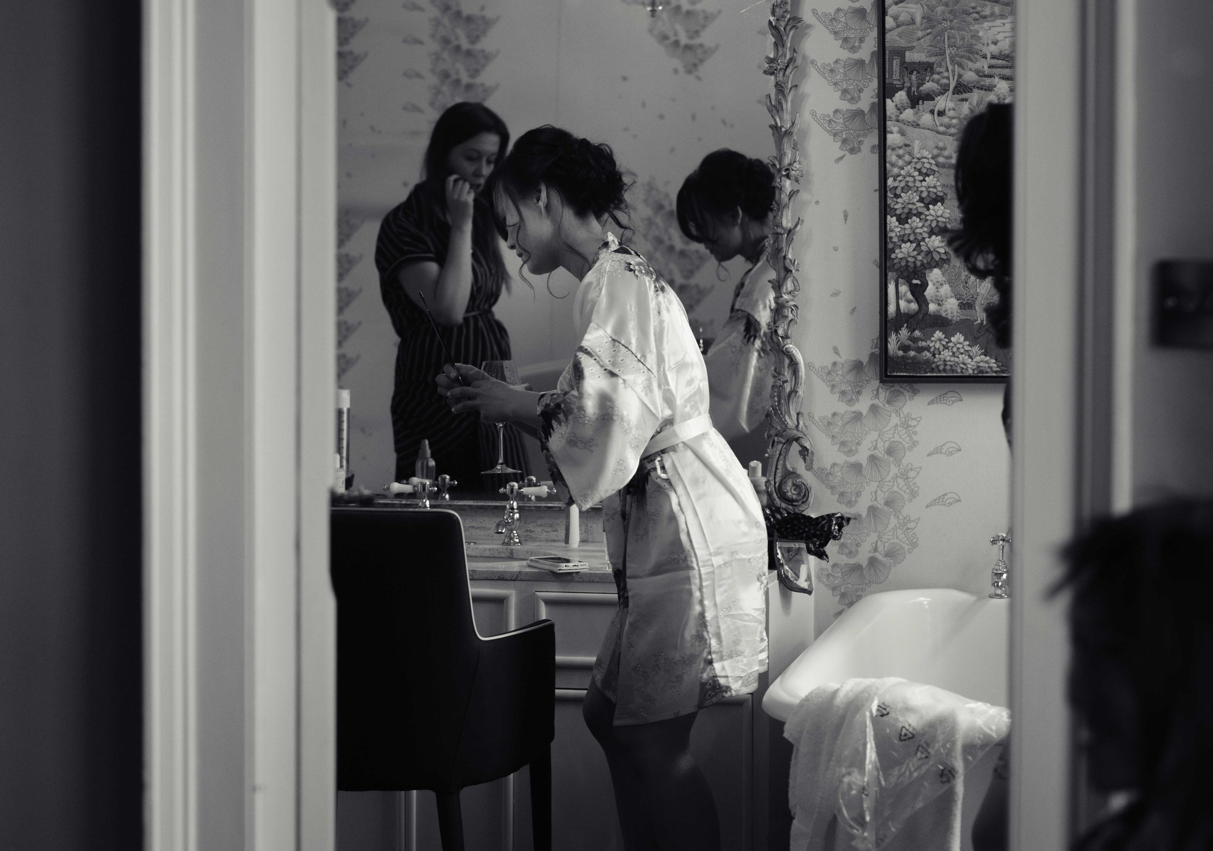 the bride and her bridesmaids getting ready in the bathroom