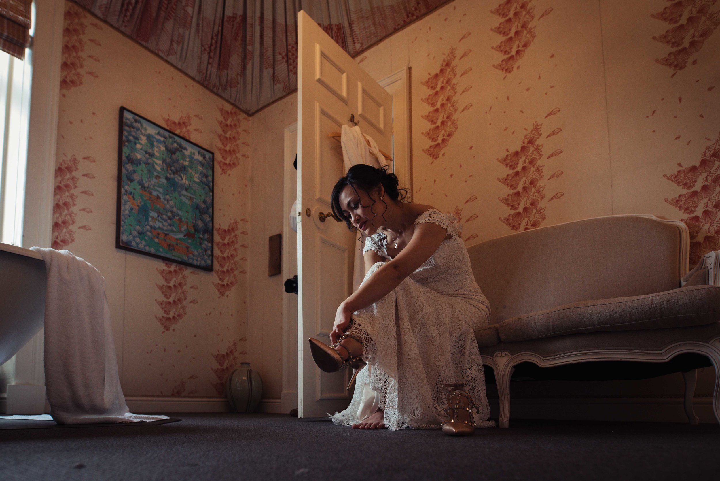 The bride puts her wedding shoes on while sitting on the sofa in her room