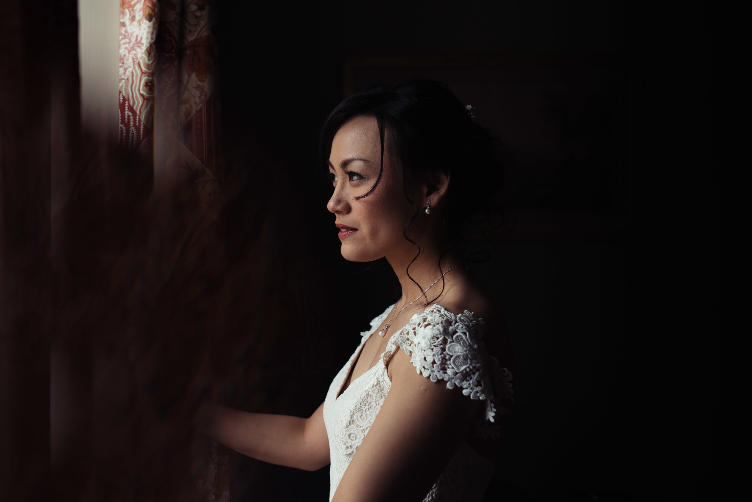 the bride stands by the window and is lit with natural light