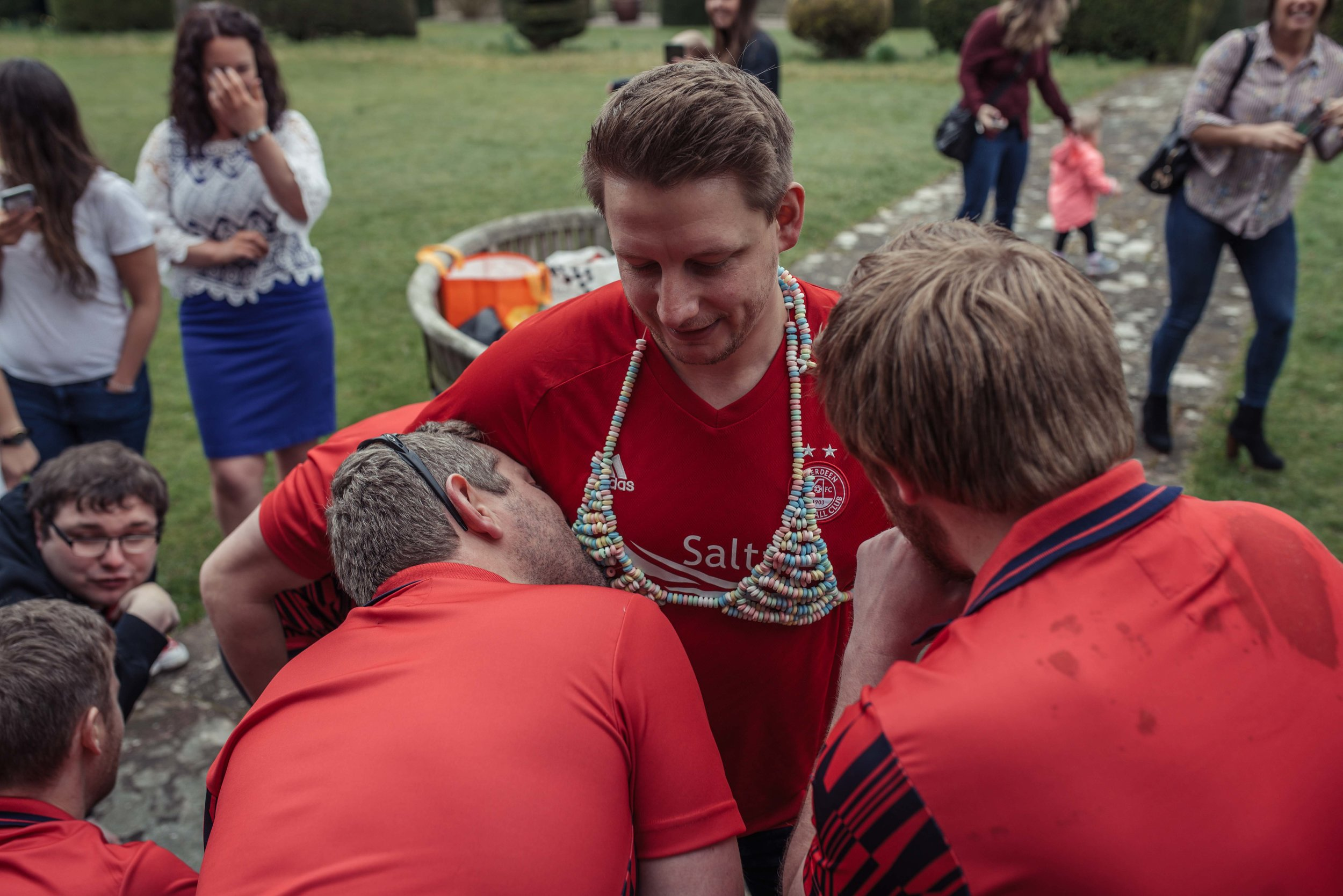 two groomsmen eat a candy bikini off the groom who is wearing a red shirt