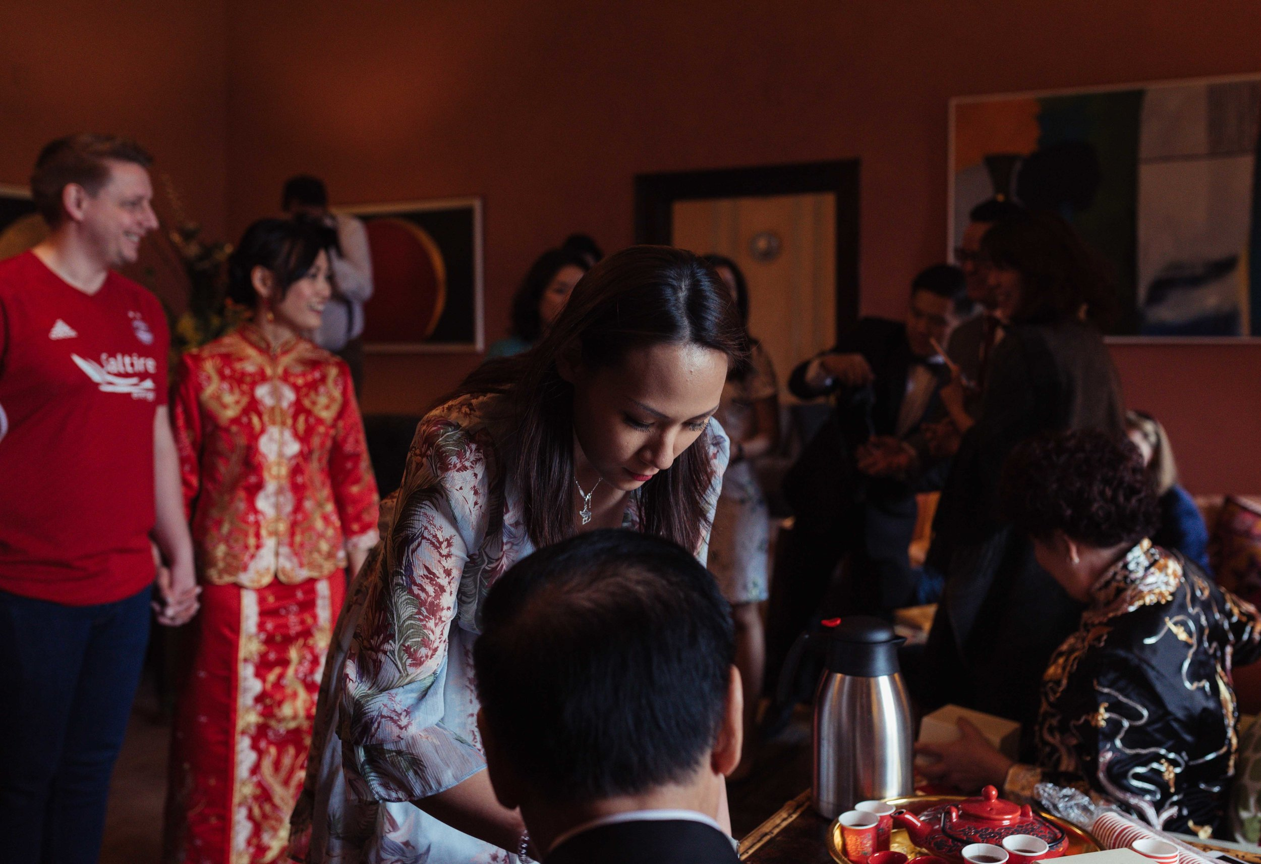 a bridesmaid serves tea at the Chinese tea ceremony