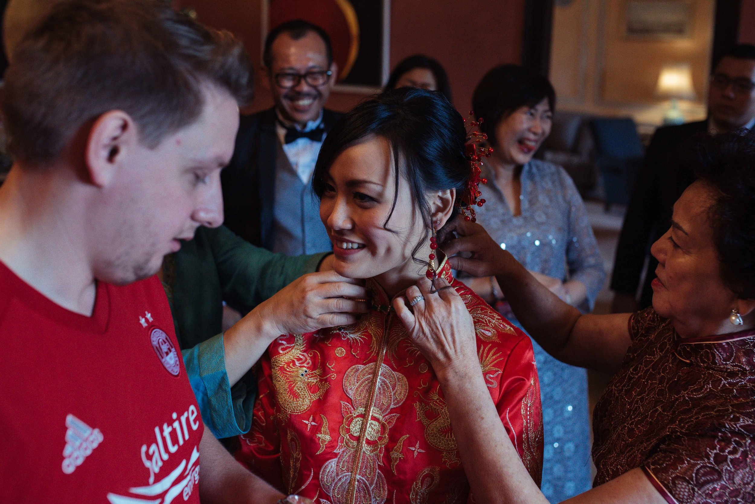 the bride puts on her new earrings during the tea ceremony at Askham Hall