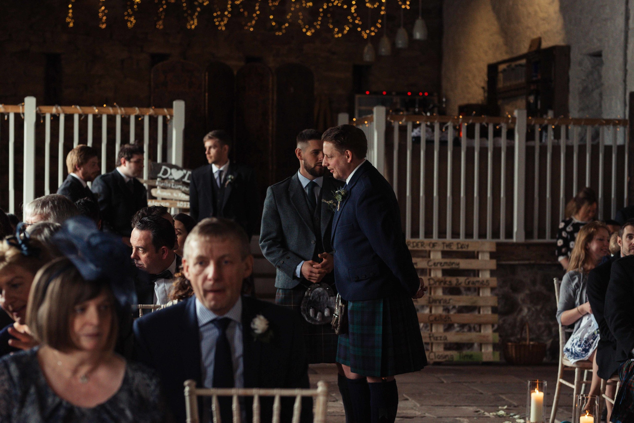 The groom stands and talks to seated guests, he's wearing a kilt