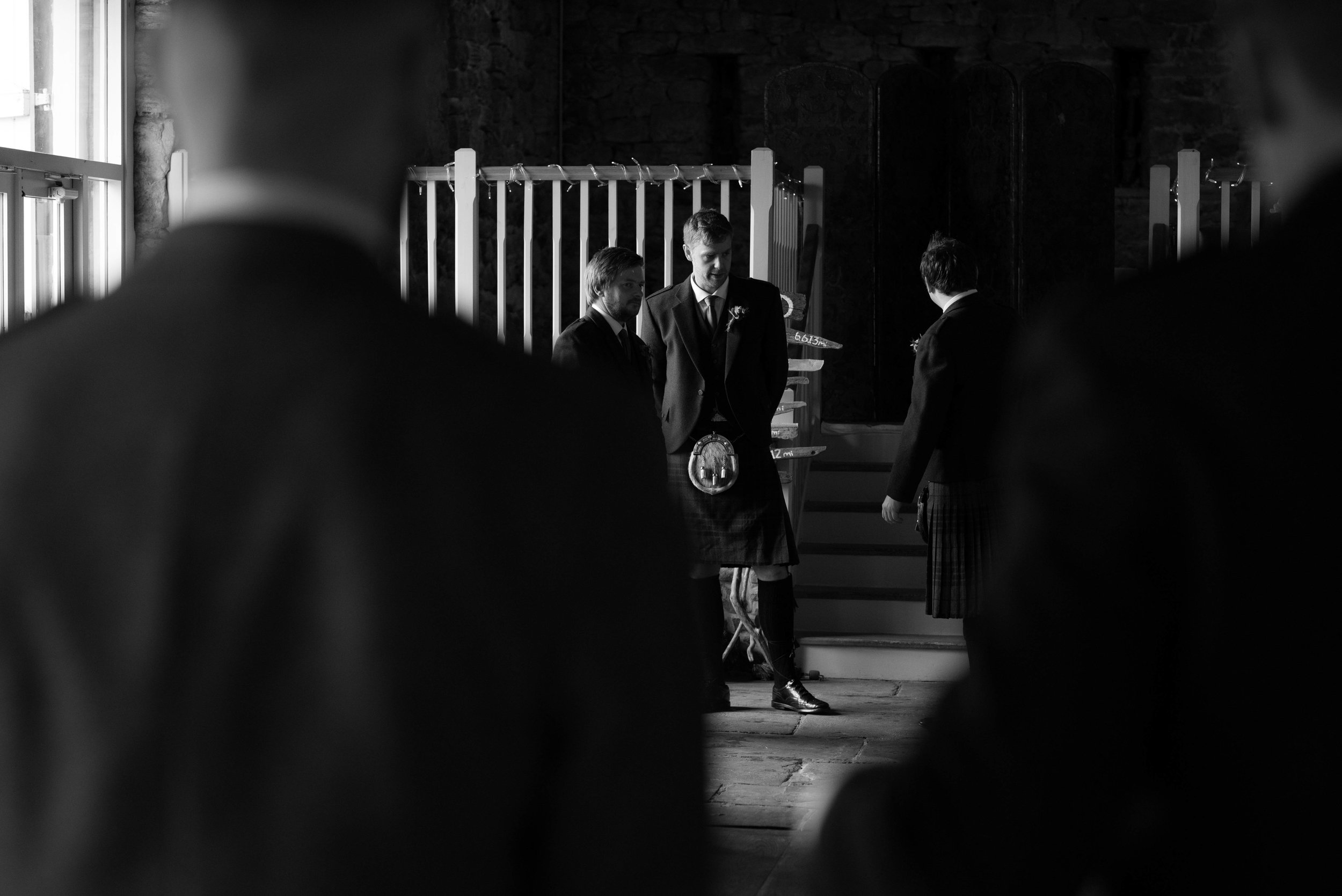 Groomsmen stand at the back of Askham Hall barn to direct wedding guests to their chairs