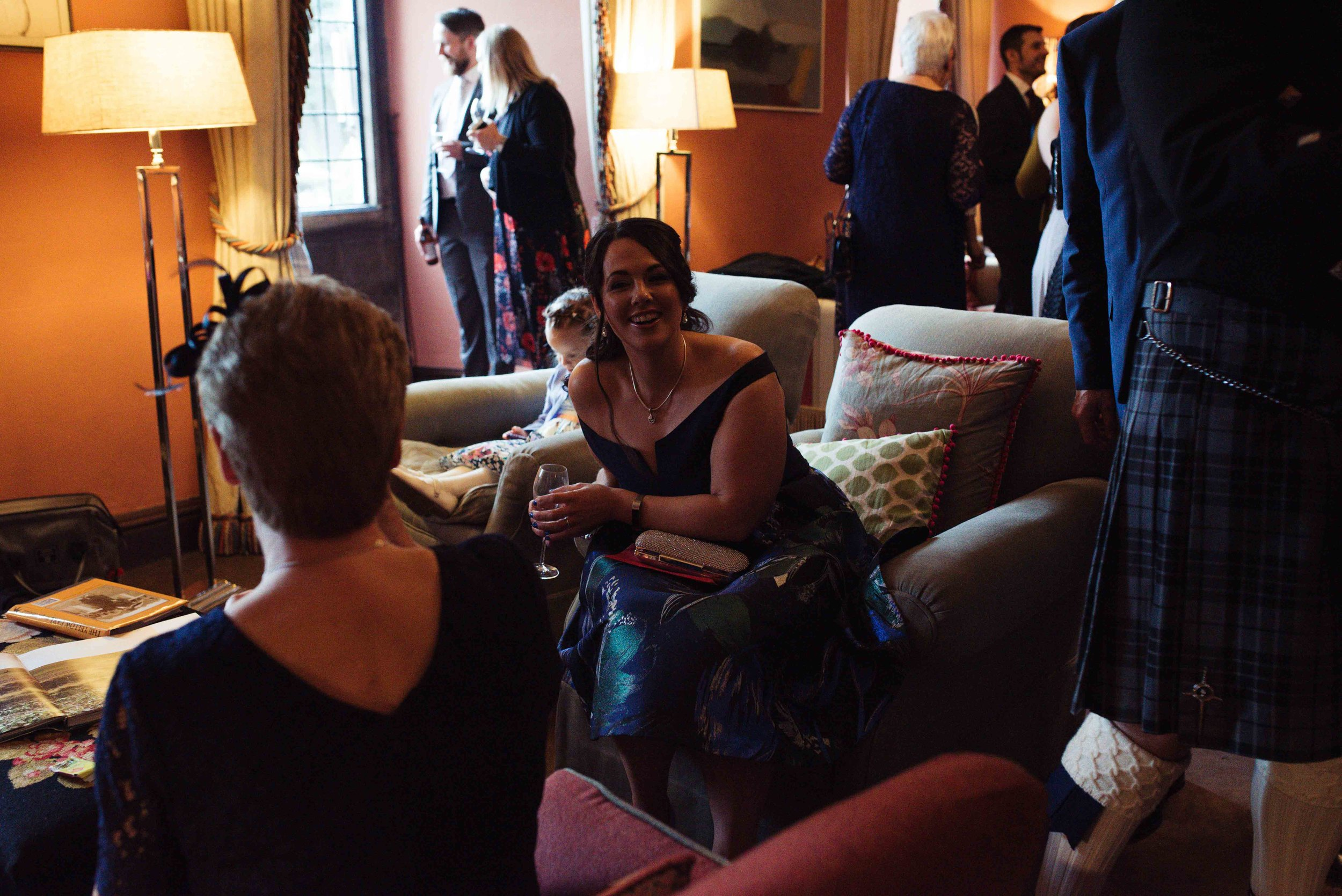 wedding guests sit on big sofas in the lounge at Askham Hall during the welcome drinks
