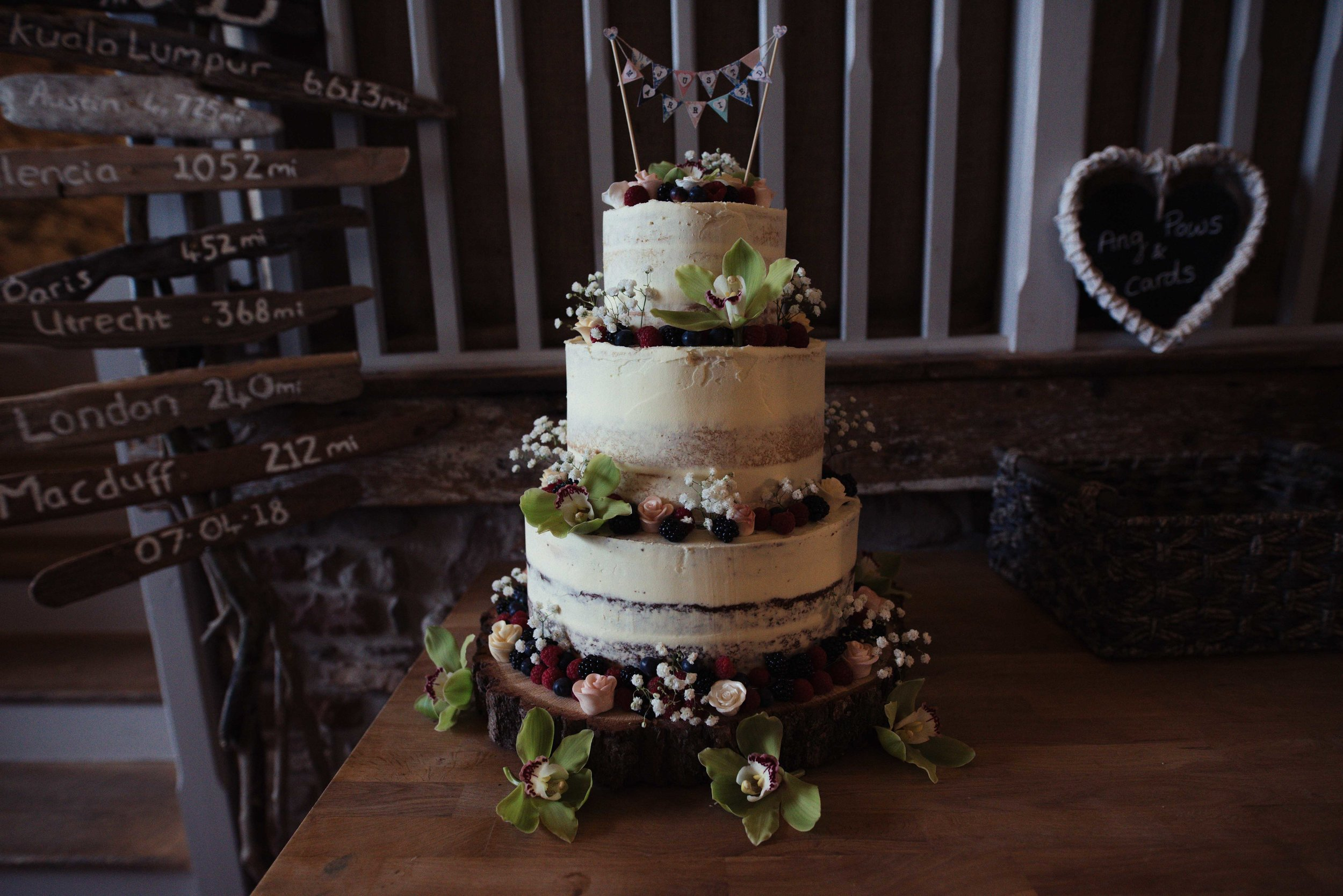The bride and groom's naked wedding cake, dressed with berries and other fresh fruit
