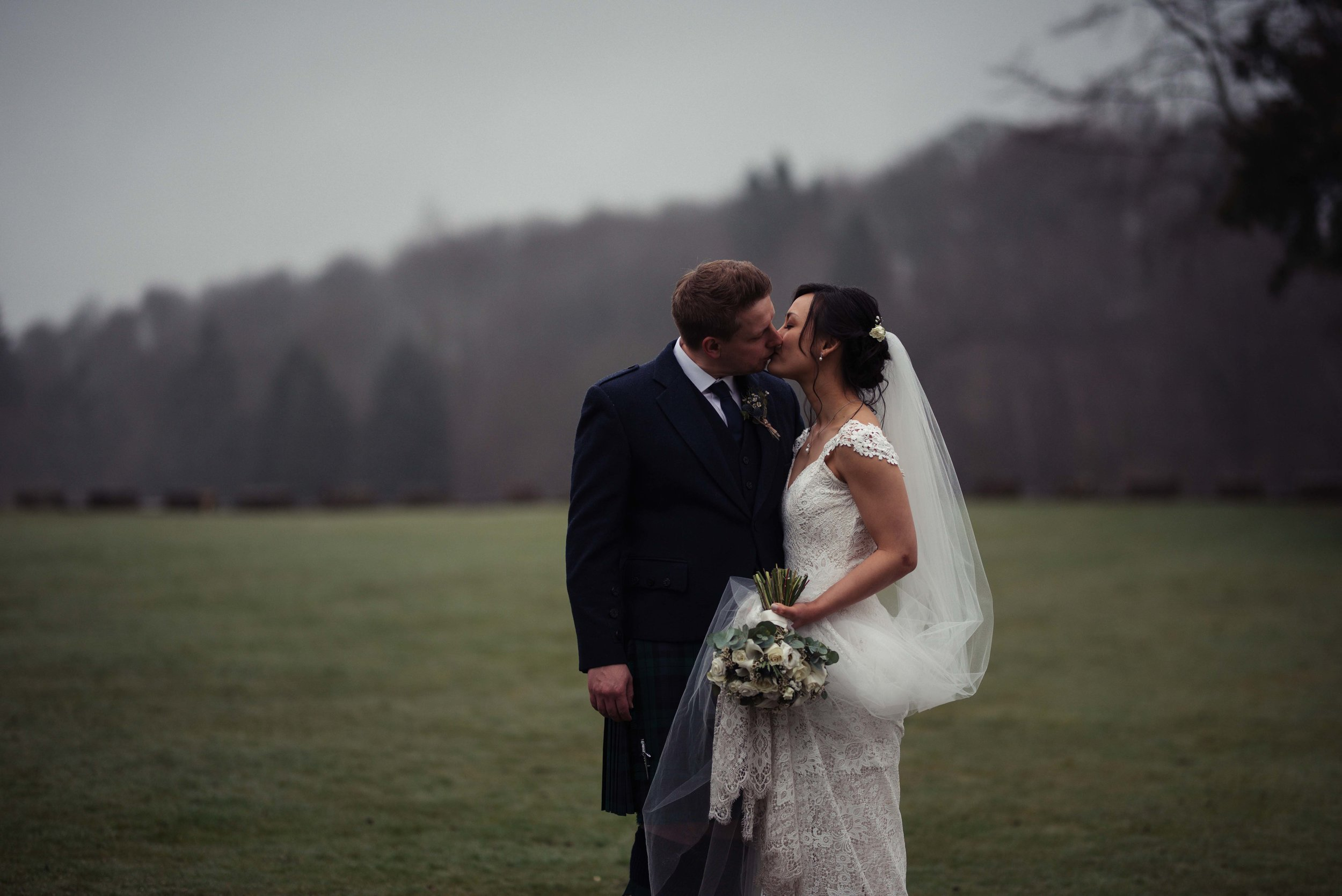 The bride and groom share a kiss together during their wedding photography