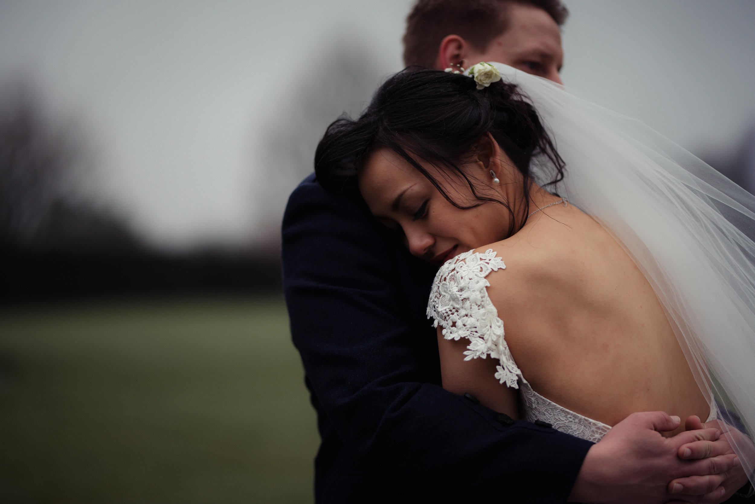 The groom pulls the bride close in to her to give her a hug during her wedding photography