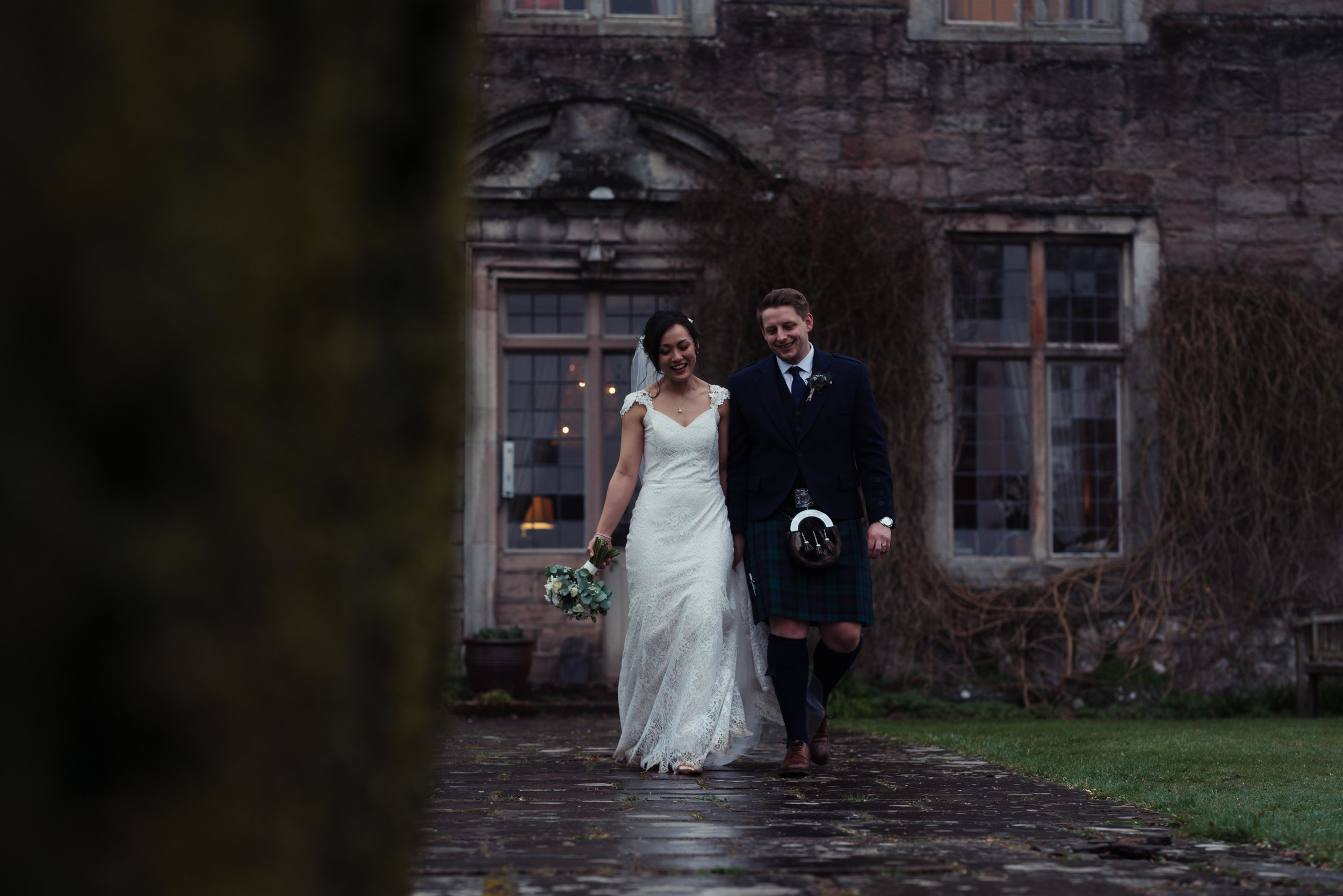 The bride and groom walking away from Askham Hall Cumbria towards the gardens