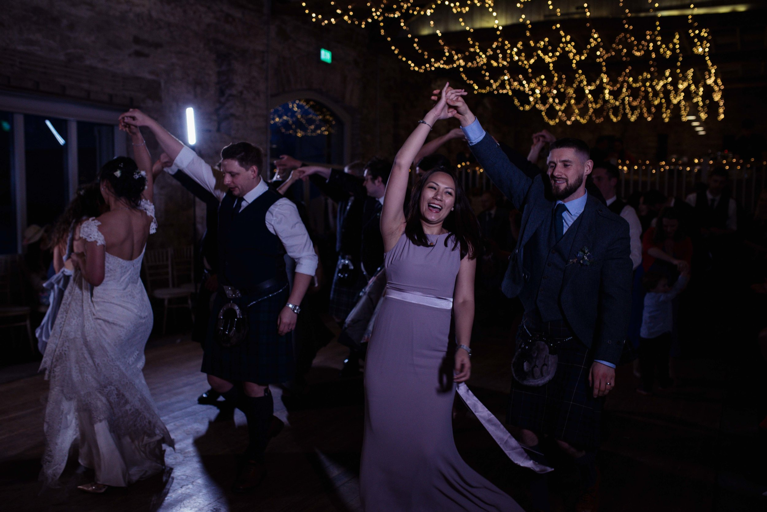 Wedding guests gather on the dance floor to continue the dancing