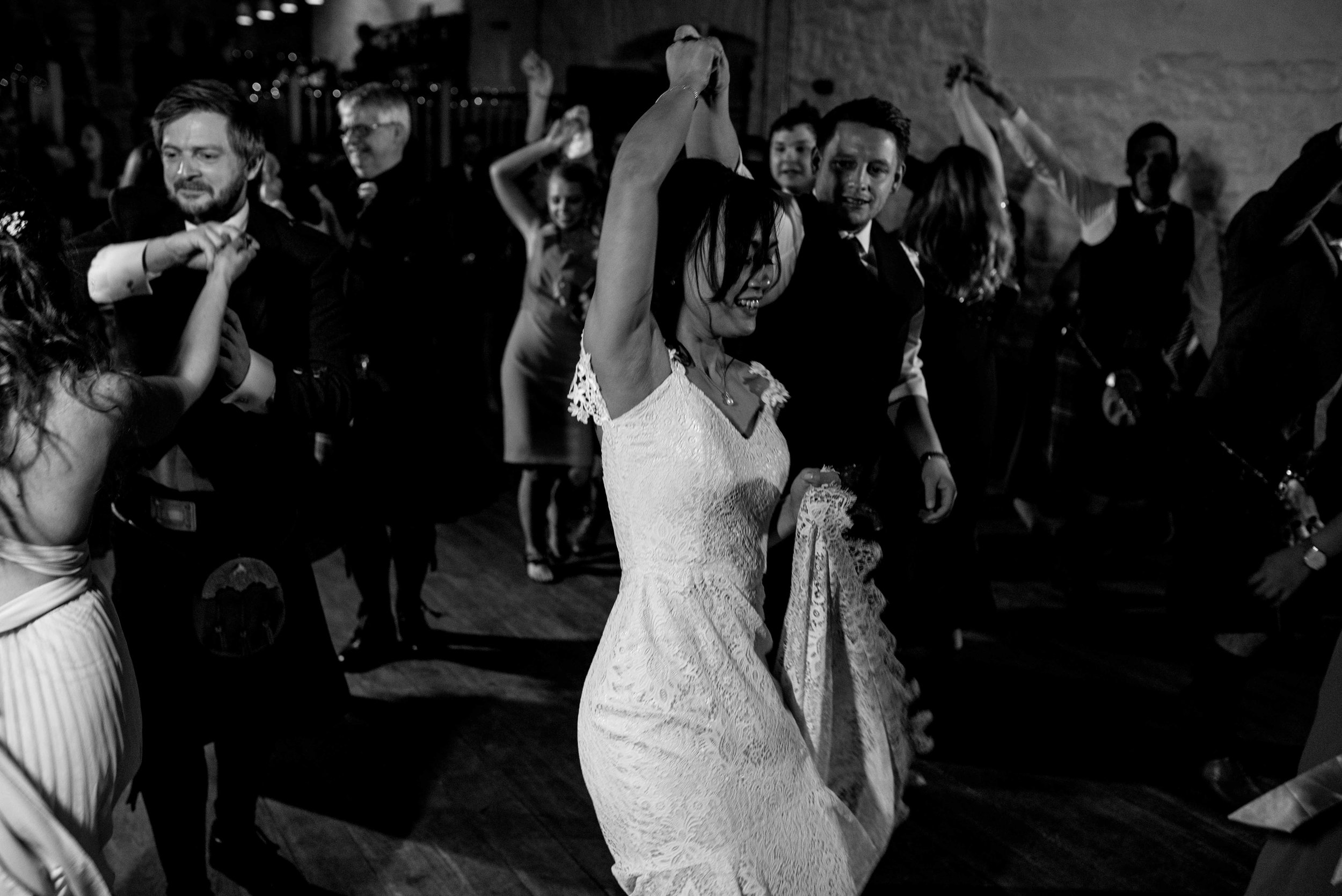 the bride raises her arms as she dances
