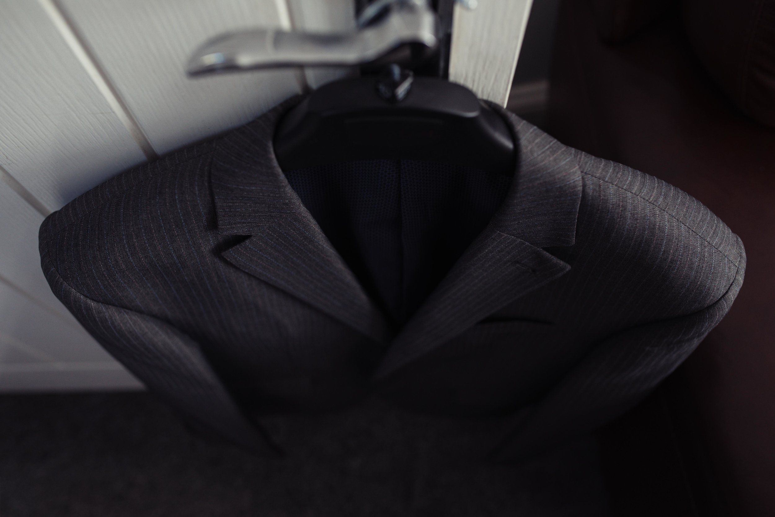 Grooms suit on a hanger hanging off the back of a door.