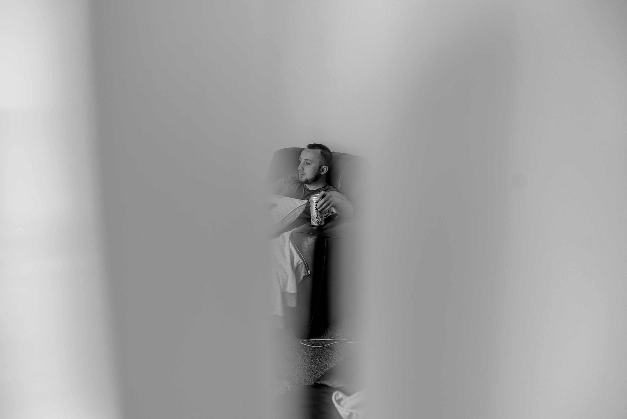 Groomsman sitting on a chair with a can of foster, taken through a crack in the door.