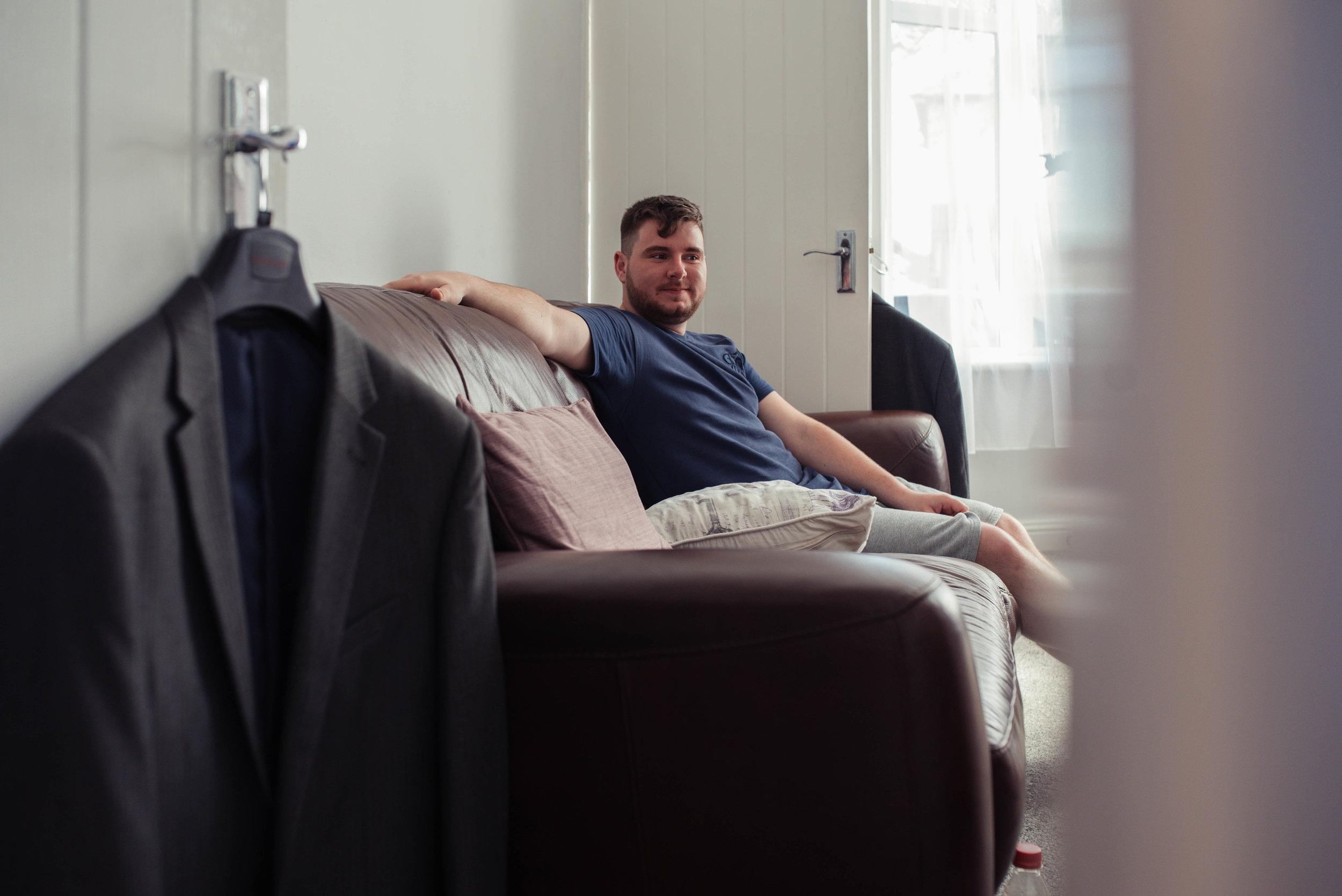 Groomsman sits on the grey sofa on the living room.