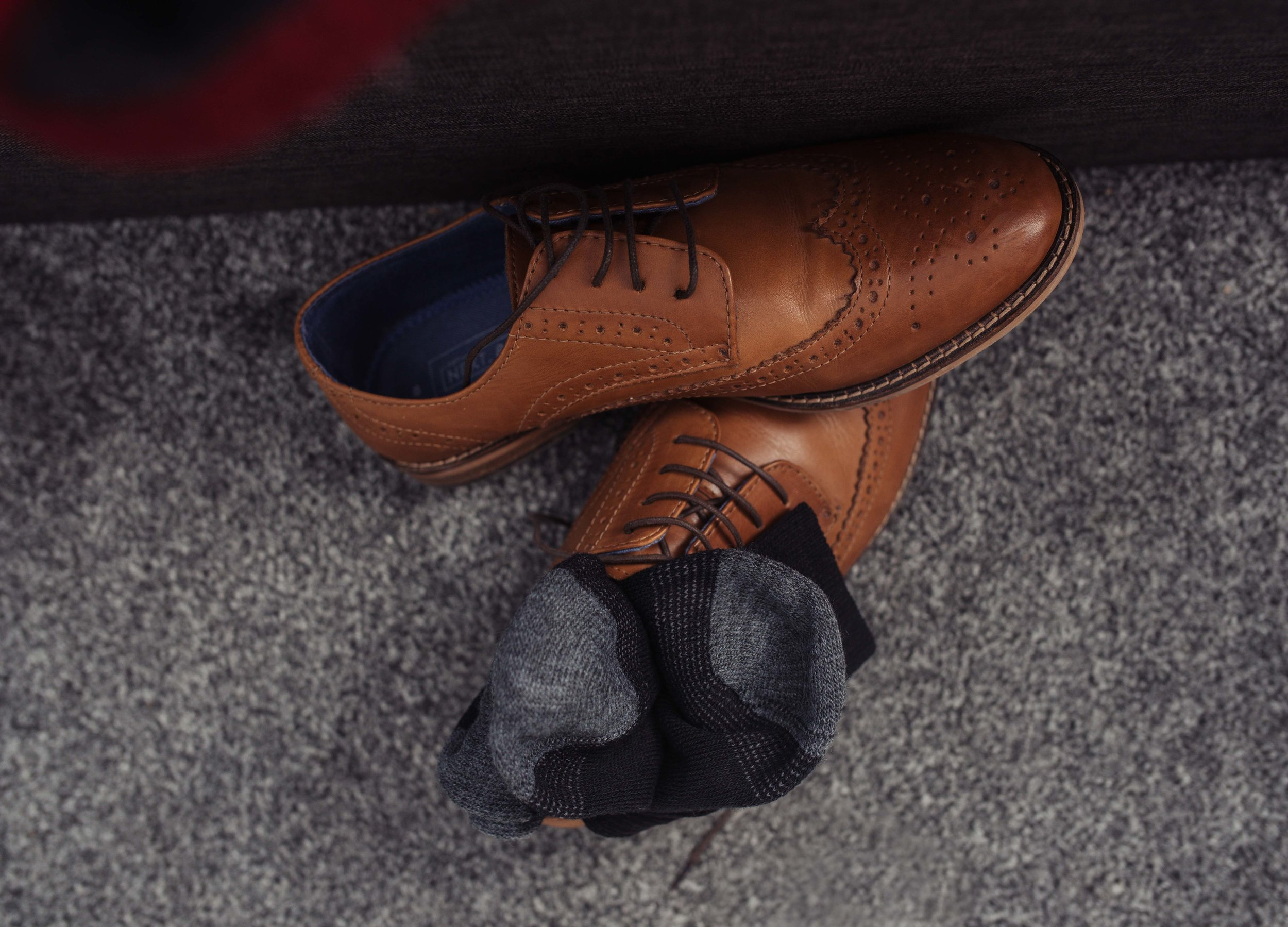 The grooms brown brogues lie on the floor with his socks on top of the shoes.