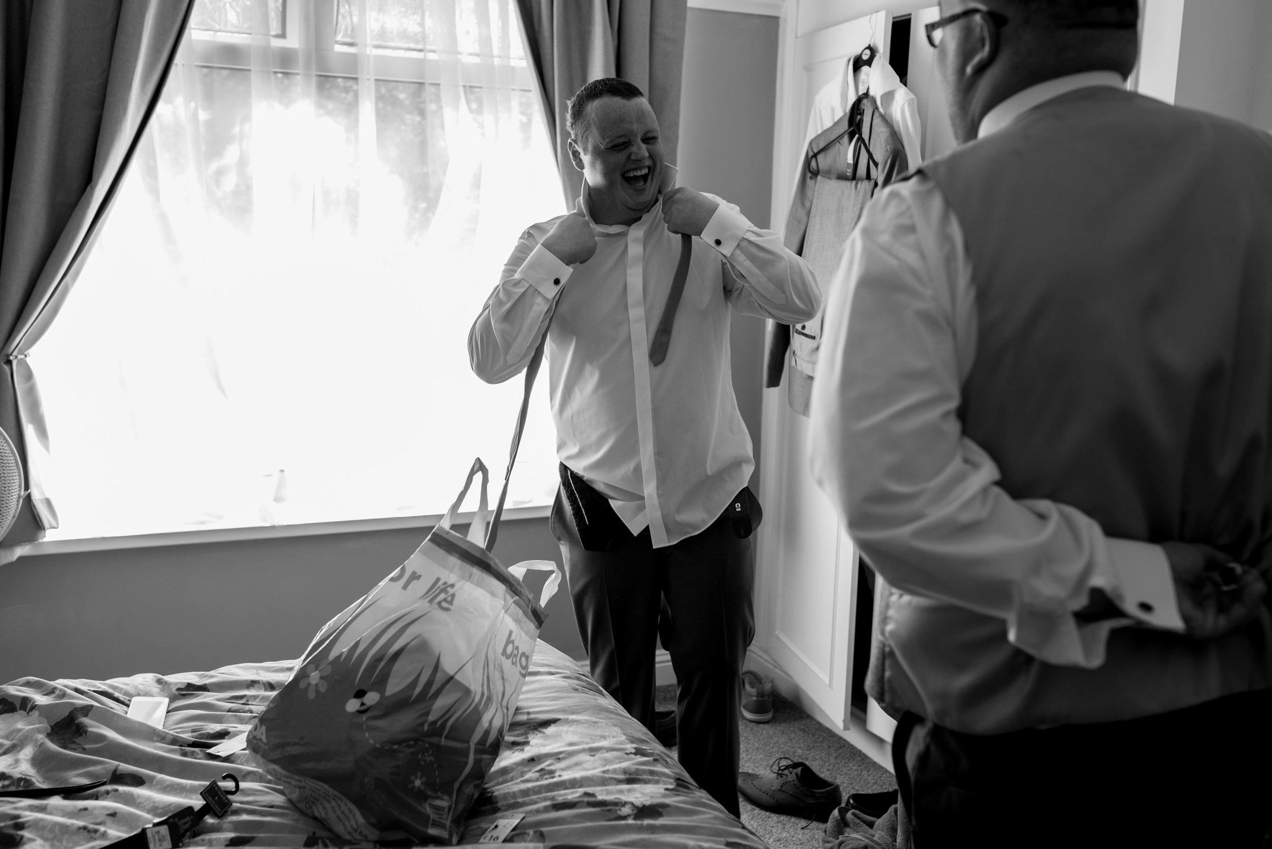Groom ties his tie while laughing towards the best man.