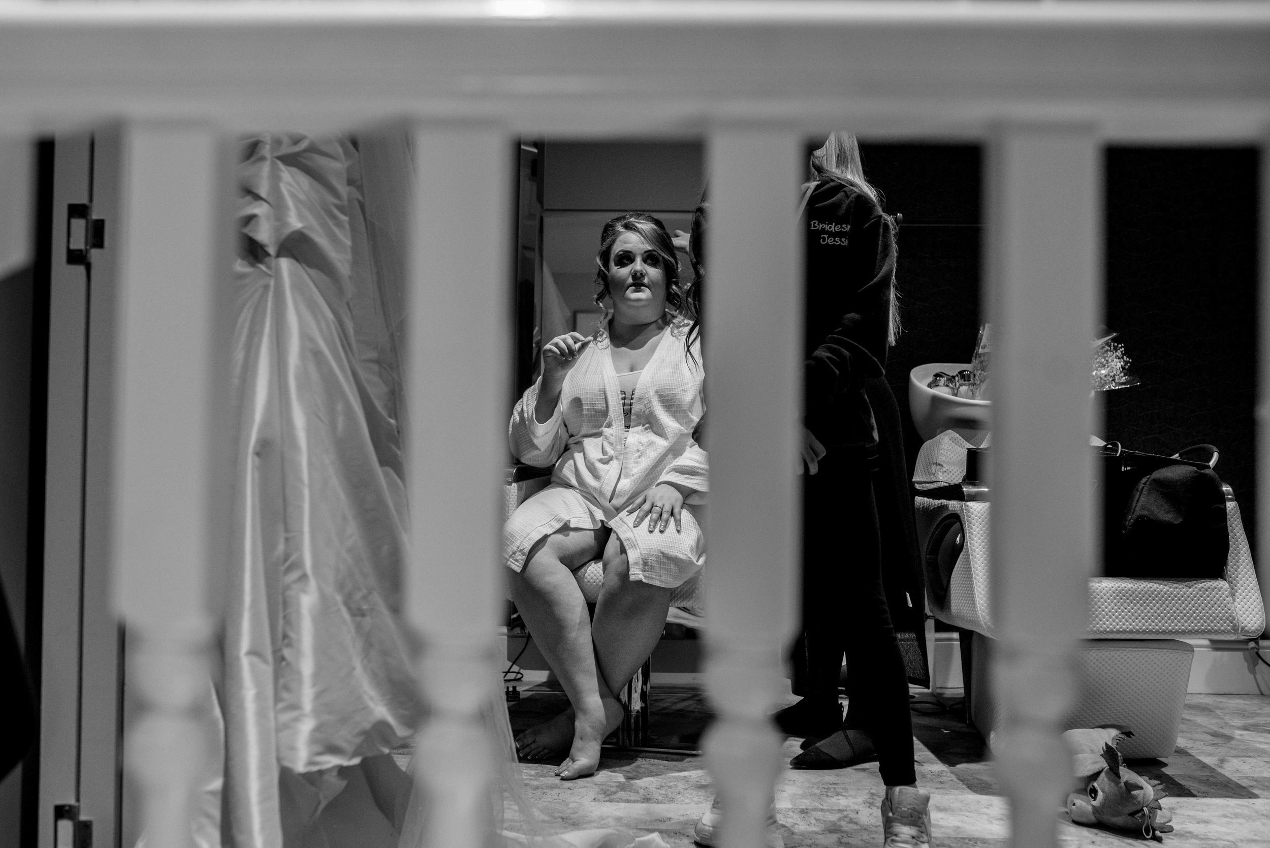 The bride is seen through gaps in the bannister rail while she gets ready for her wedding.