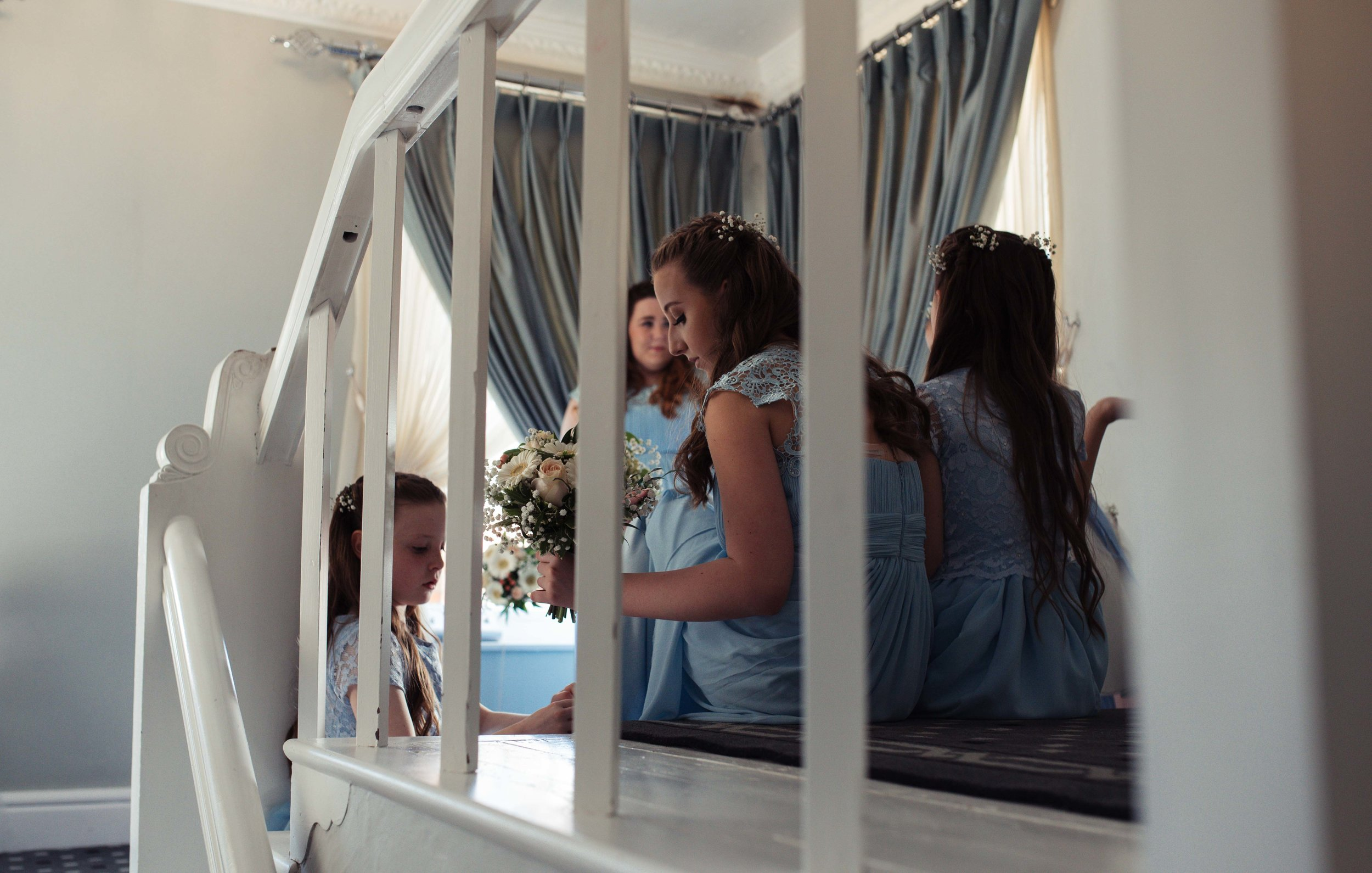 Flower girls and bridesmaids sit on the stairs of the wedding venue and wait for the bride to appear.